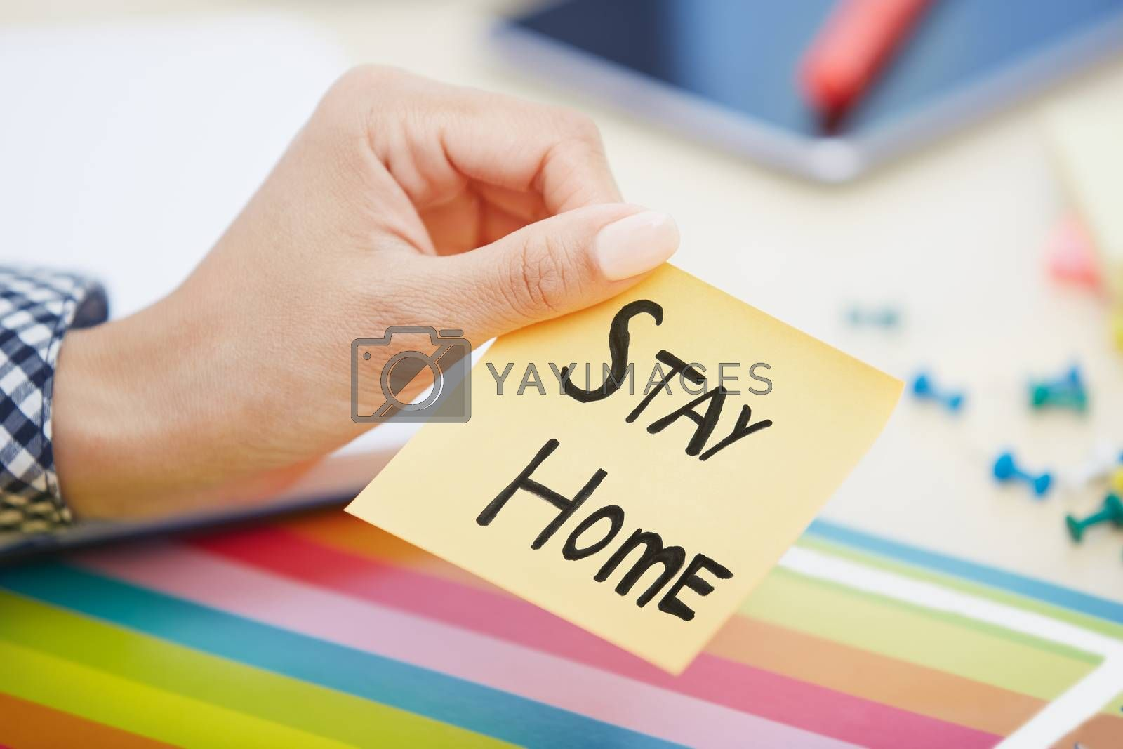 Human hand holding adhesive note with Stay Home text