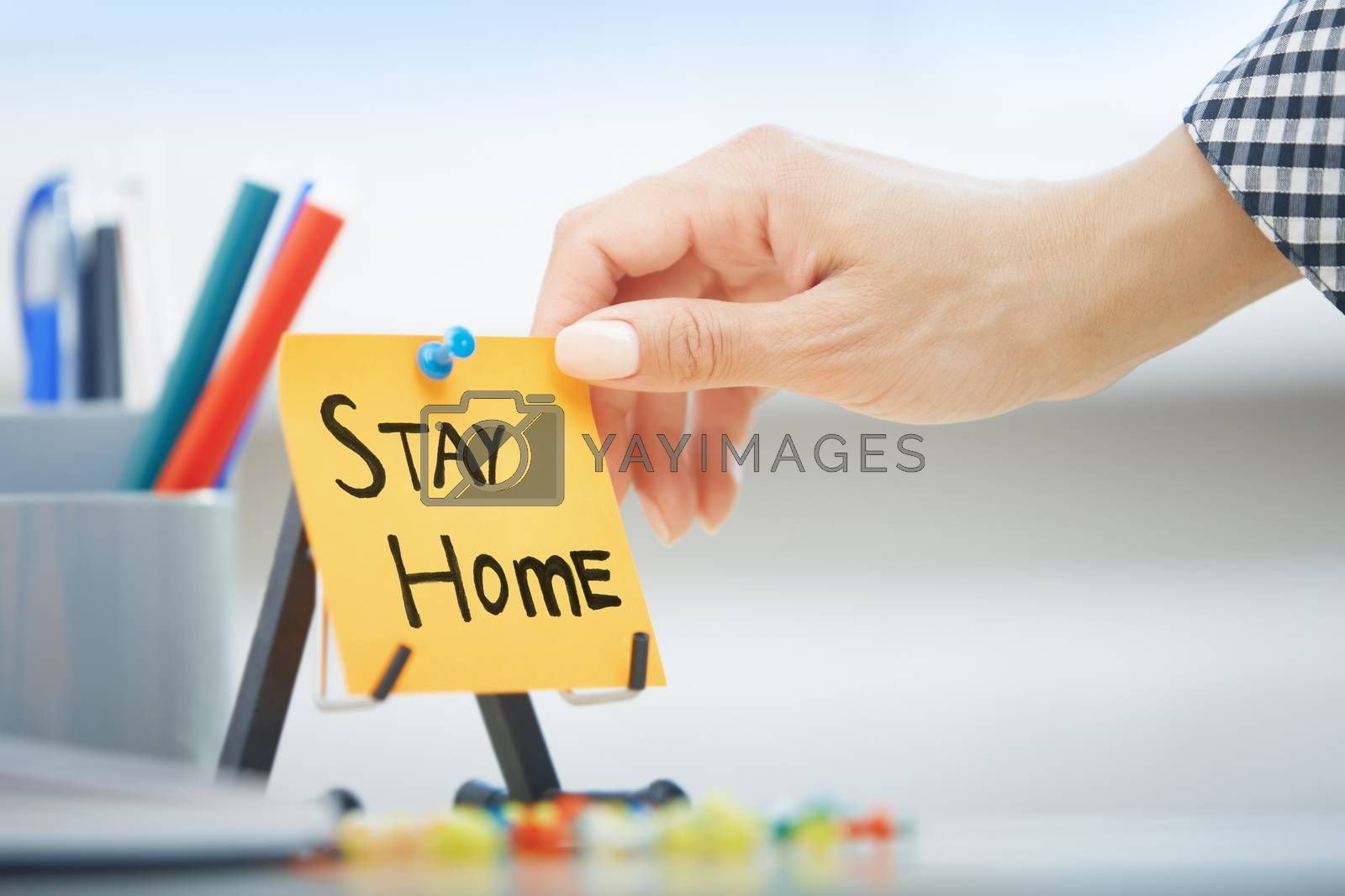 Human hand holding adhesive note with Stay Home order