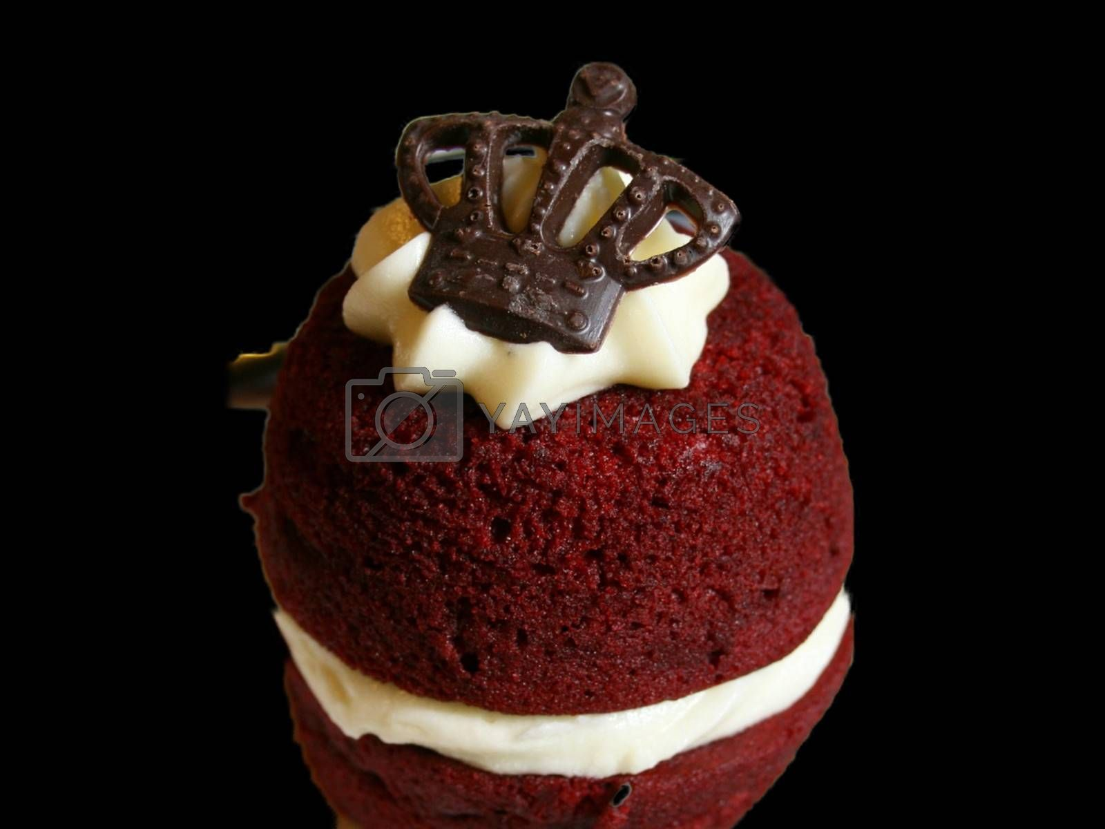 Royalty free image of Closeup of a red velvet cake topped with a chocolate crown isolated on black background by balage941