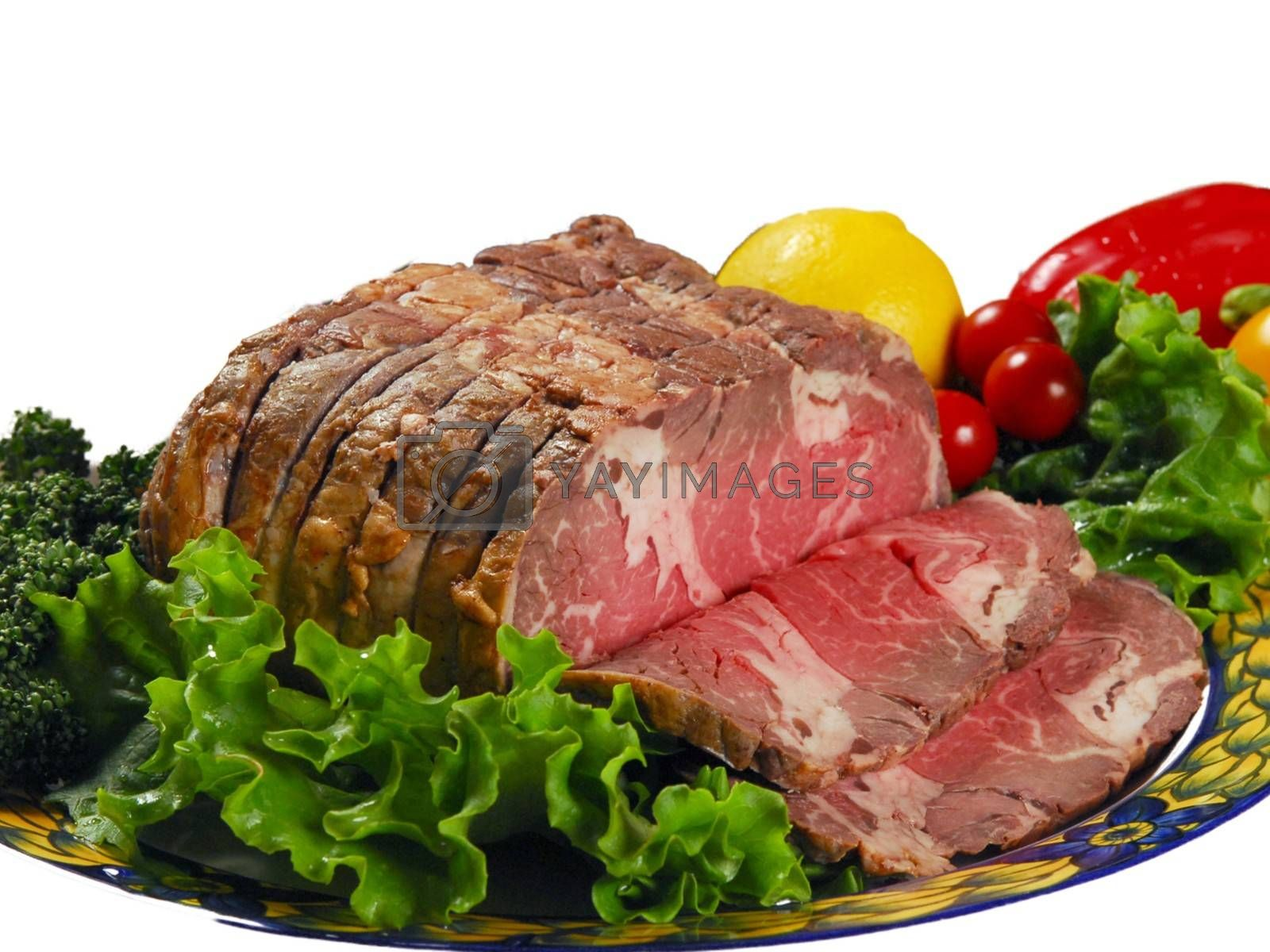 Royalty free image of Knuckle ham with fresh salad, broccoli, lemon,California peppers on a plate by balage941