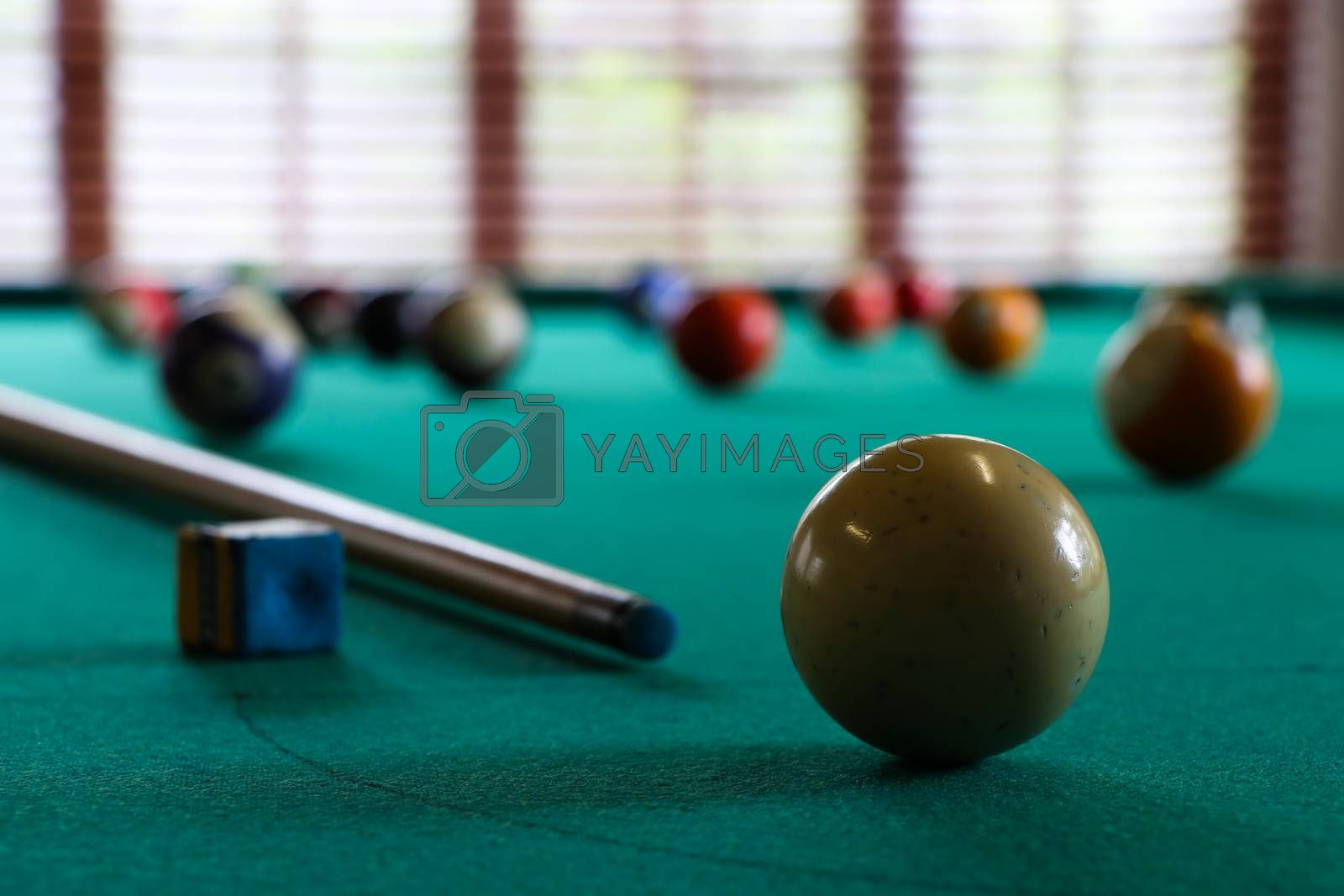 A white cue ball and stick with chalk block on green felt surface of a pool table, South Africa