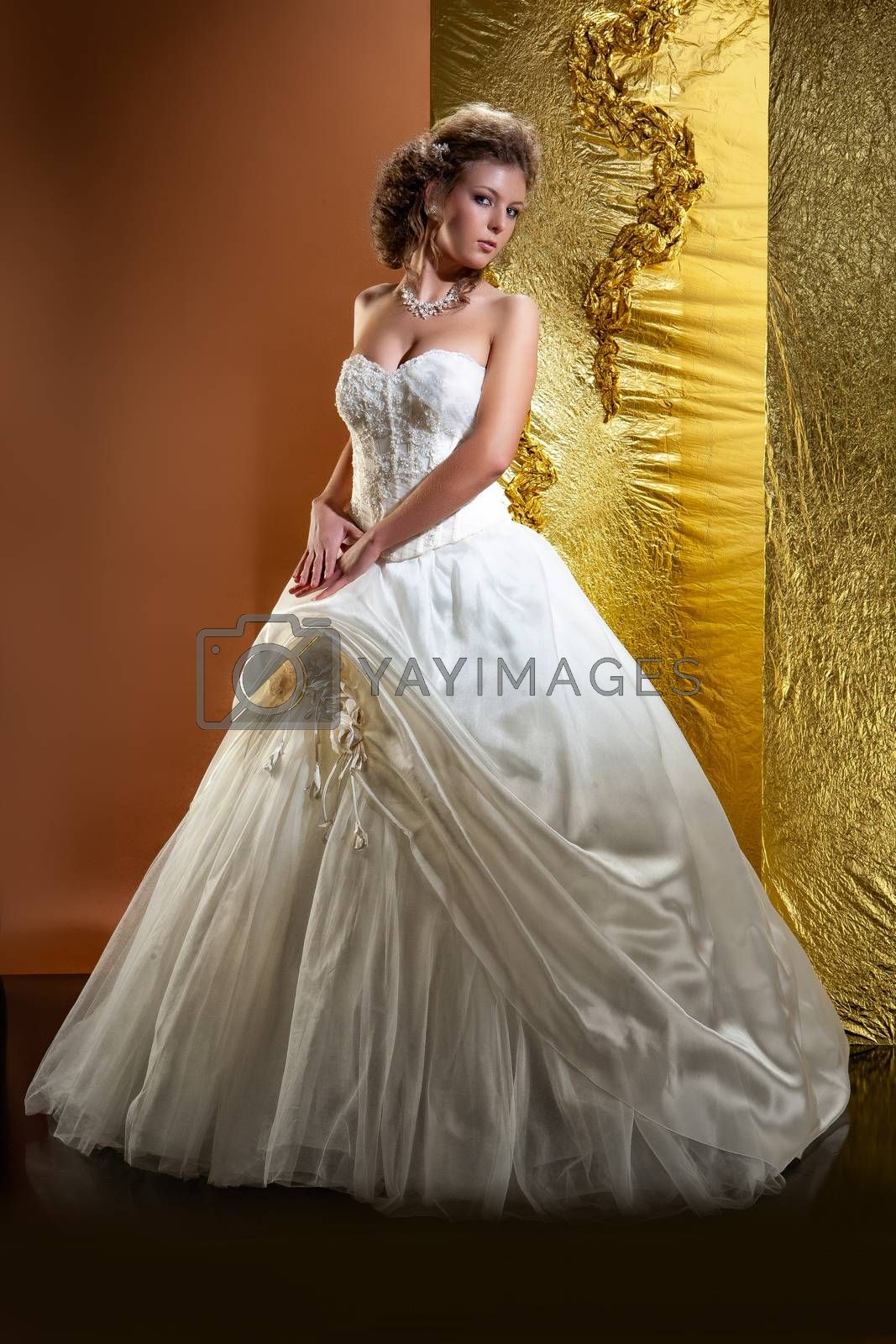 Young woman in a wedding dress on a studio background