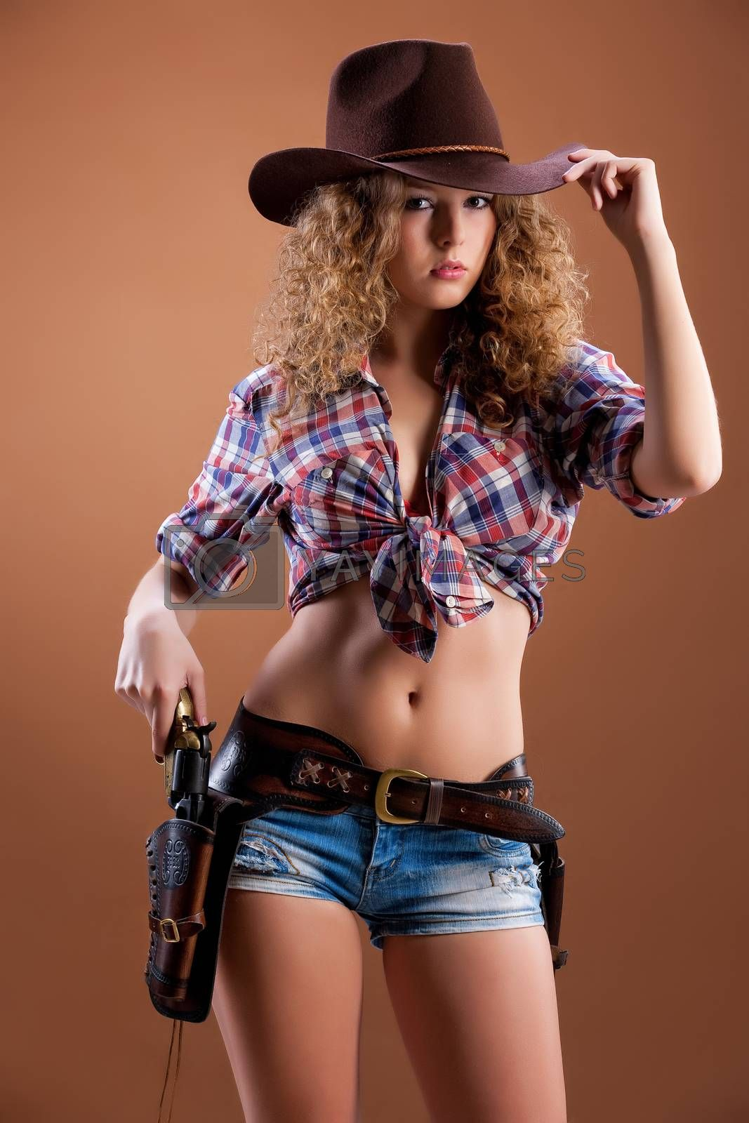Young woman dressed in a western style with a revolver