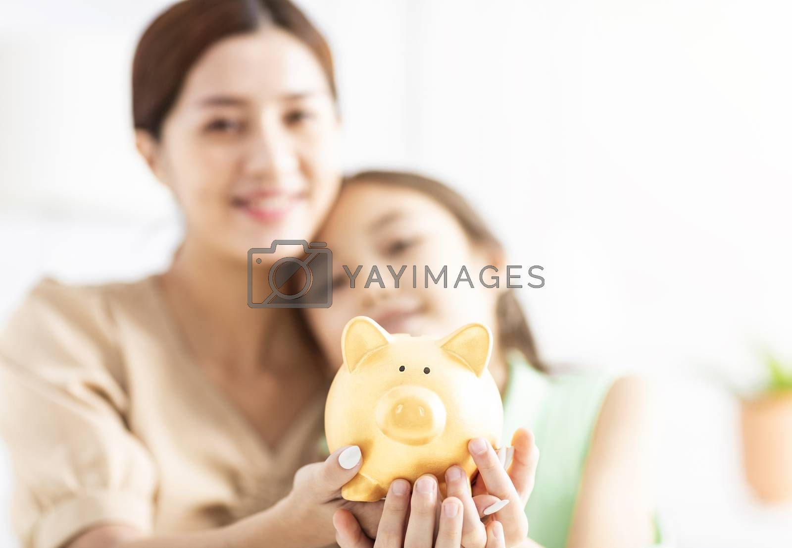 Mother and her daughter holding piggy bank