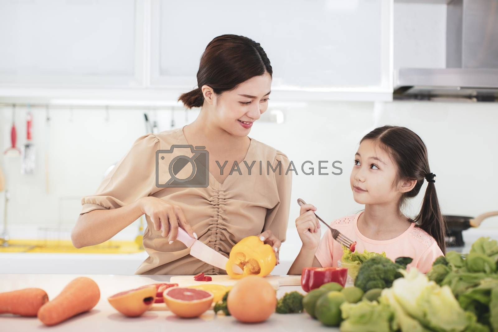 happy Mother and child daughter  eating the vegetables and fruit