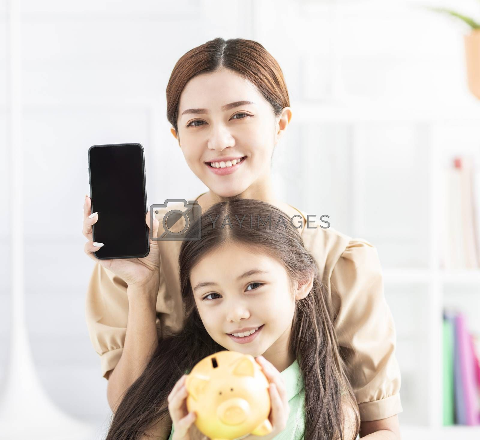 happy mother and daughter showing the mobile phone and piggy bank