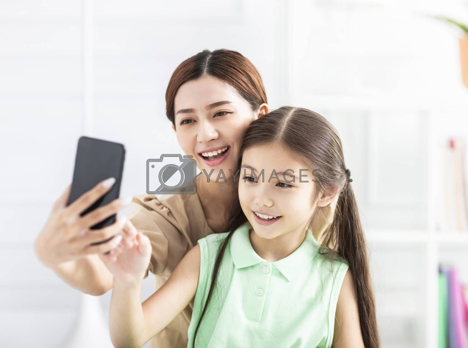 happy mother and daughter taking selfie by  smart phone