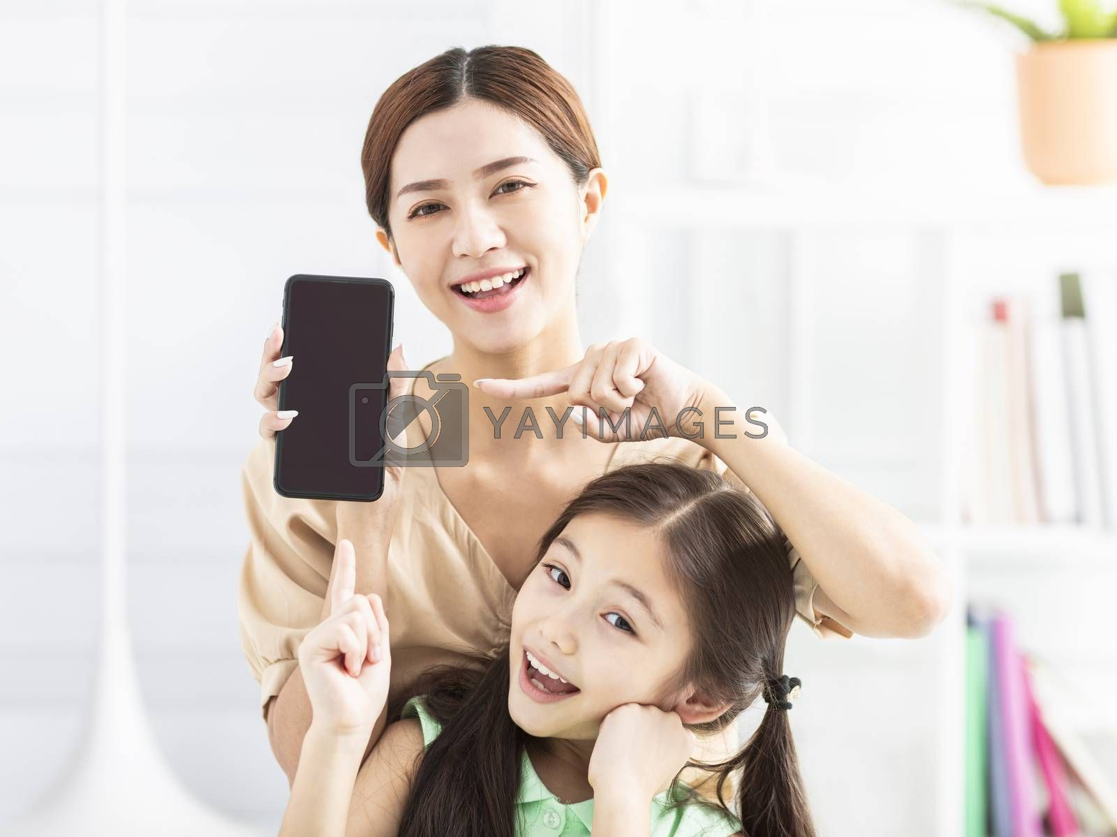 happy mother and daughter showing the mobile phone