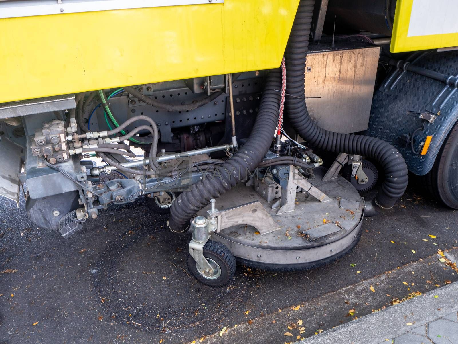 a car for cleaning roads with round brushes on a city street.