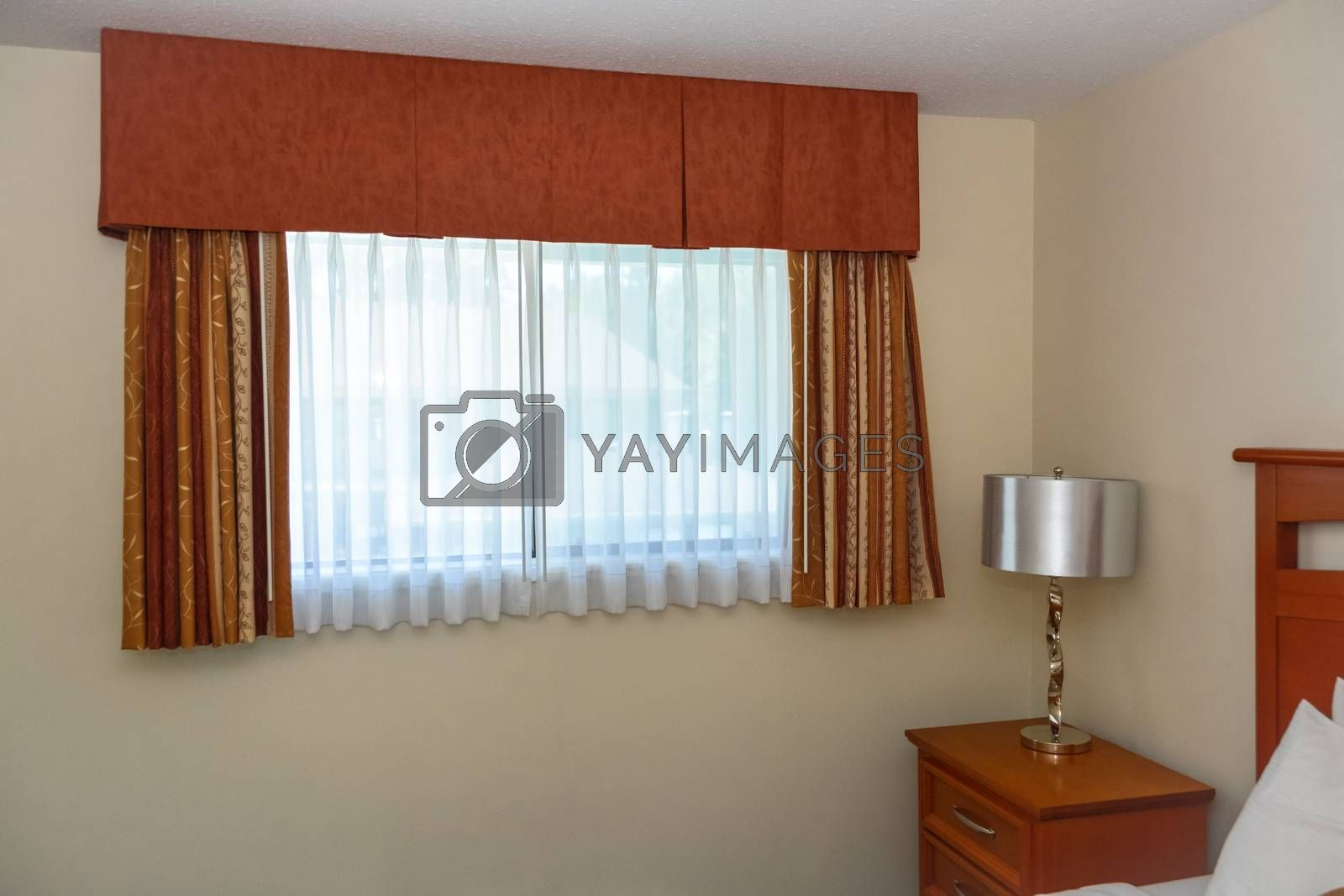 Bedroom window with the curtains and bedside table in the corner of the room