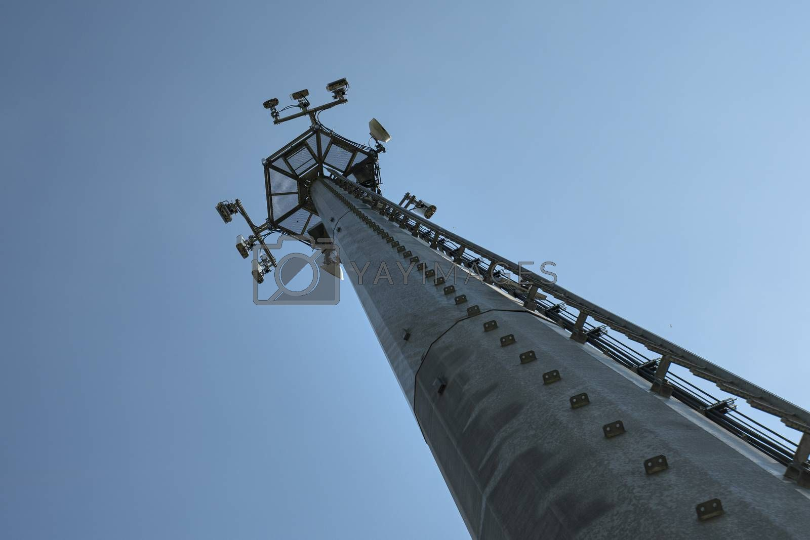 bottom view of a metal pylon with cell phone antennas