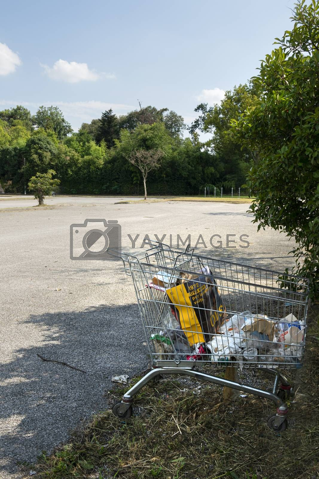 a supermarket trolley with rubbish abandoned in a parking lot