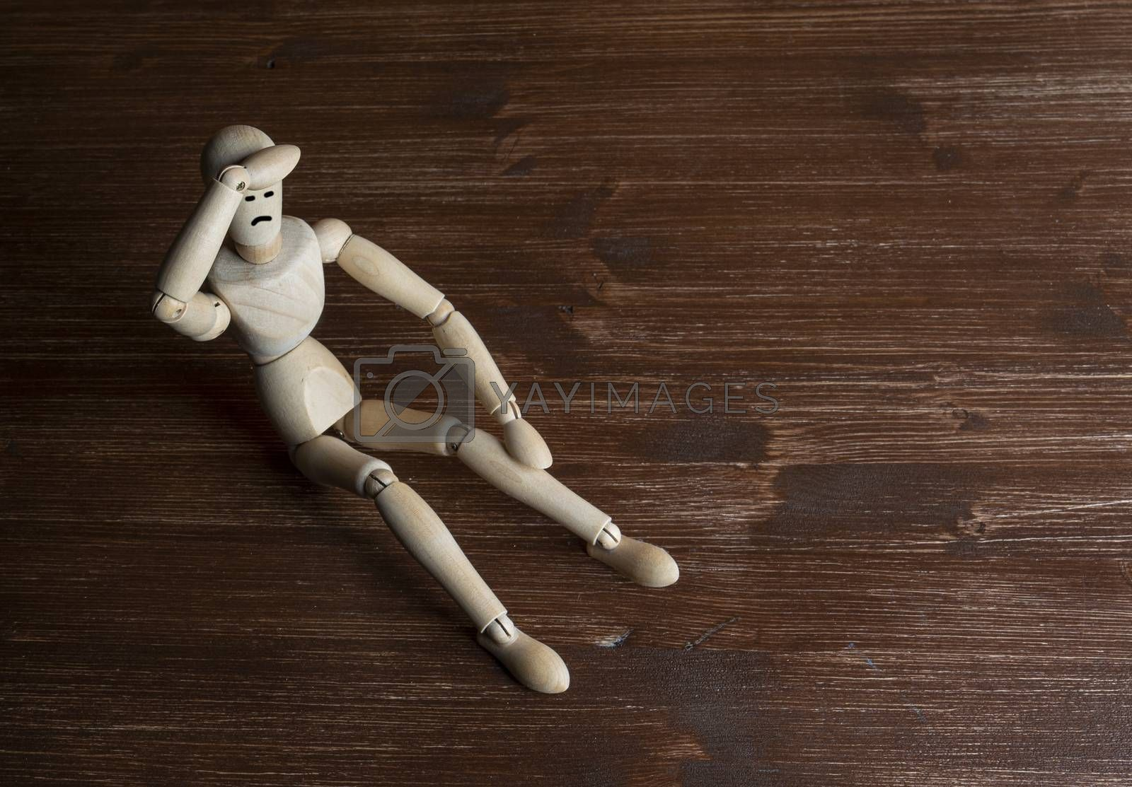 a wooden mannequin with his hands on his head in despair