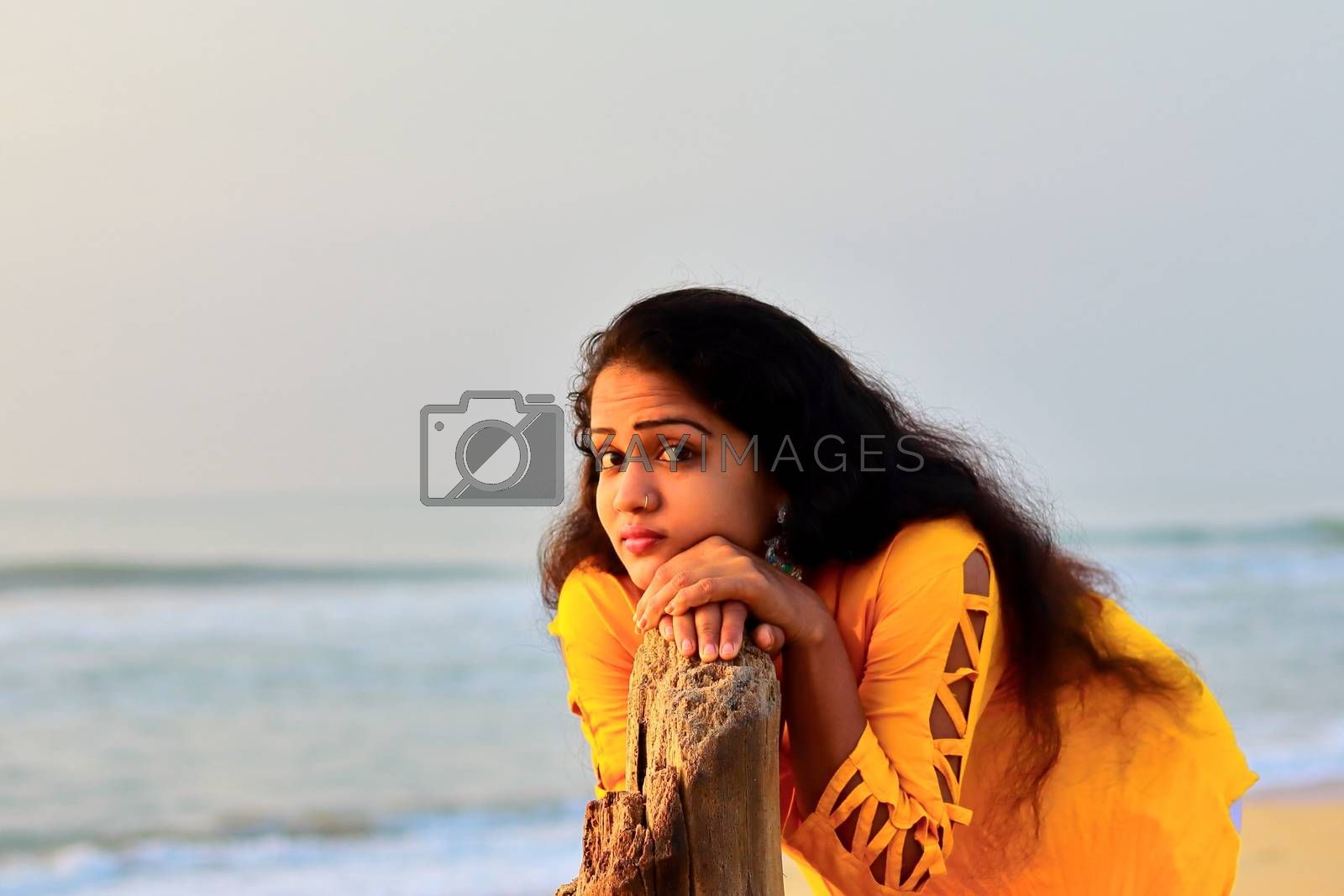 A gorgeous girl standing on the seashore with the help of dry tree wood, outdoors portrait