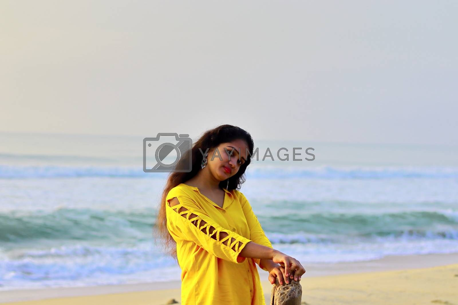 A stylish girl standing on the seashore holding a dry tree wood