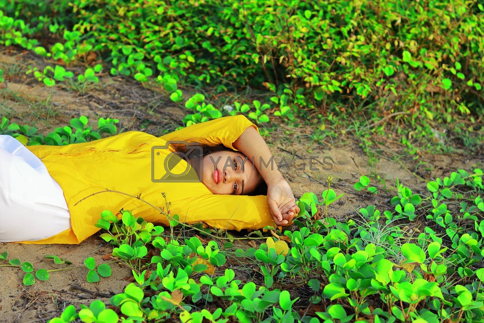 A fashionable young girl lying on the ground among green leaves
