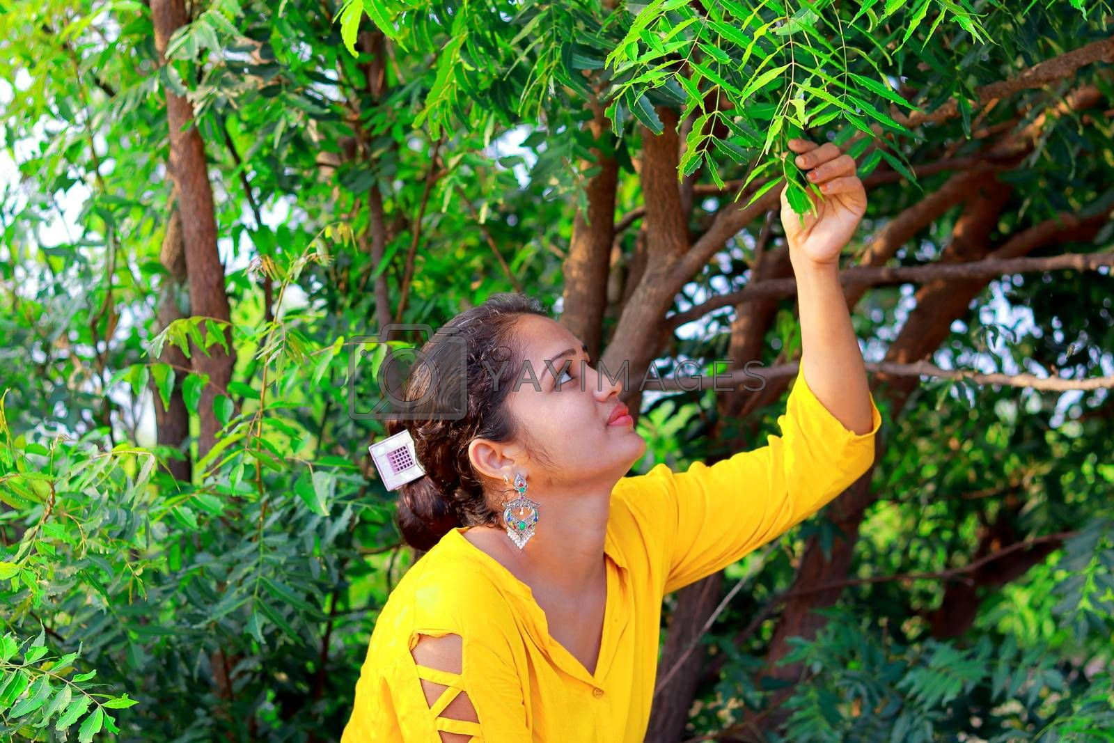 A fashionable Indian model girl sitting under a neem tree and touching fresh leaves with her hands