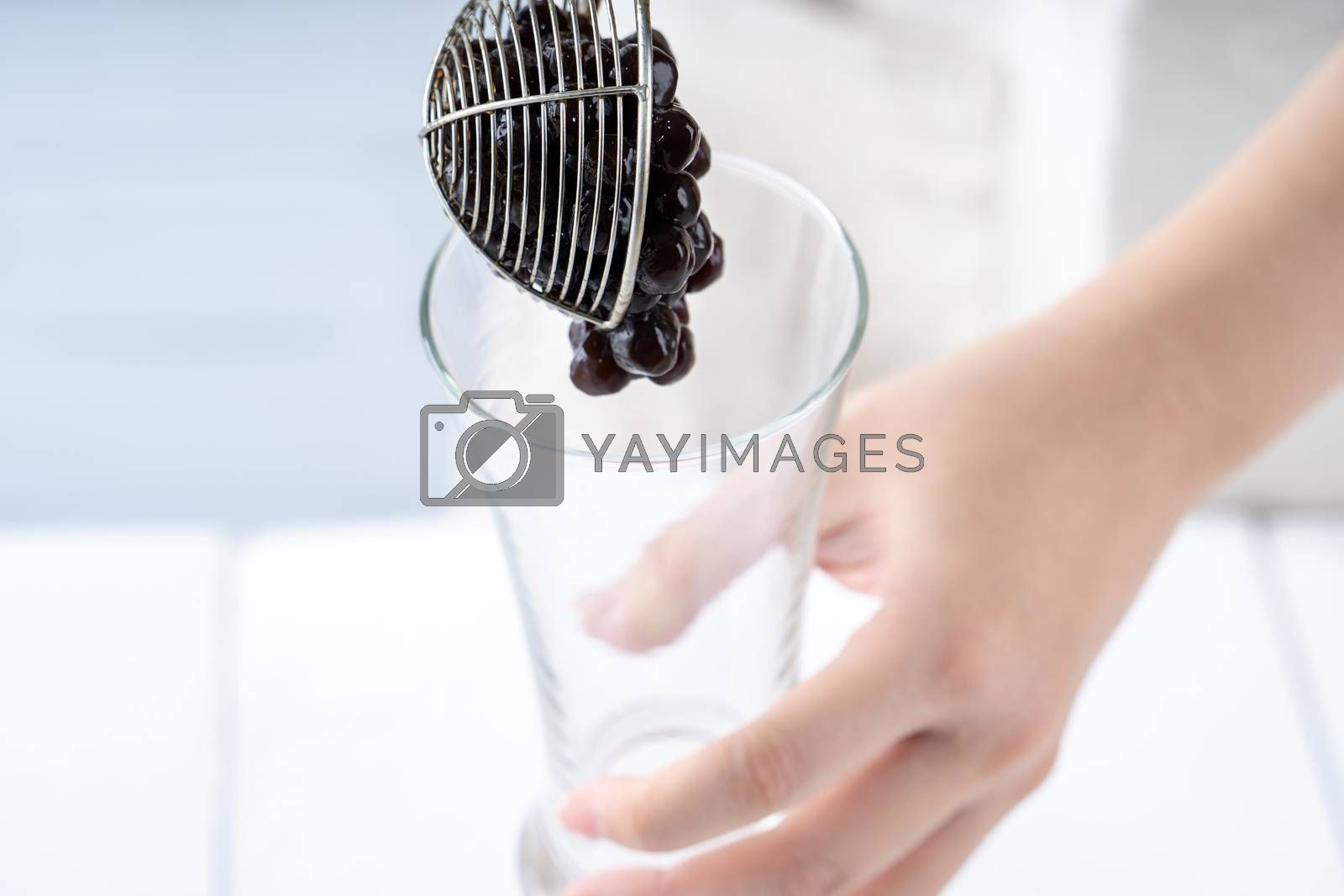 Making bubble tea, scoop and pour cooked brown sugar flavor tapioca pearl bubble balls into cup on white wooden table background, close up, copy space.