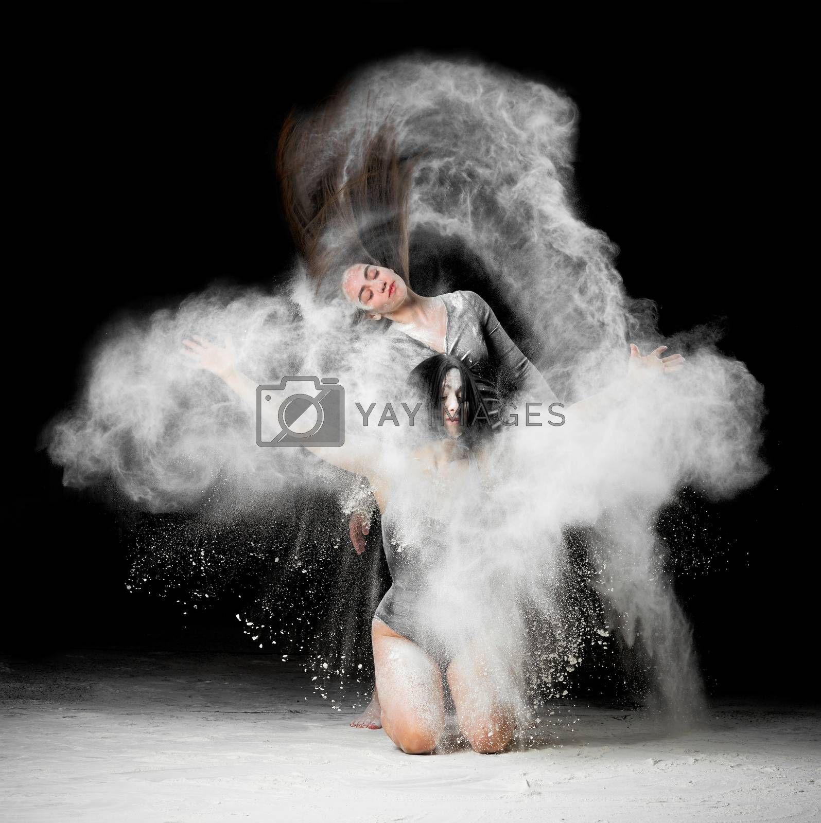 two beautiful young caucasian women in black bodysuits with a sports figure are dancing in a white cloud of flour on a black background, explosion and expresse in motion