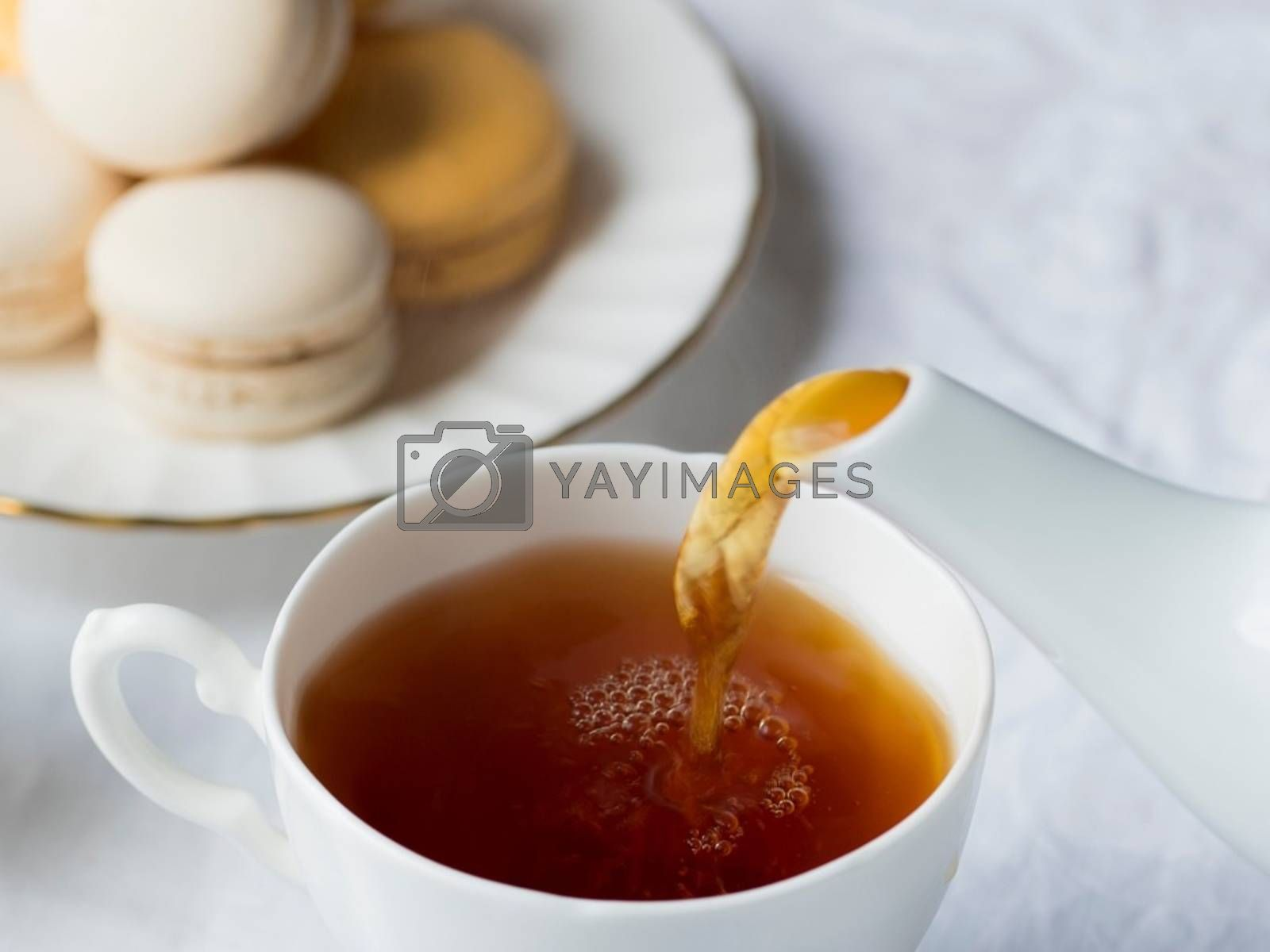 Royalty free image of Snapshot of tea and delicious tea cakes poured out of the jug on the table by balage941