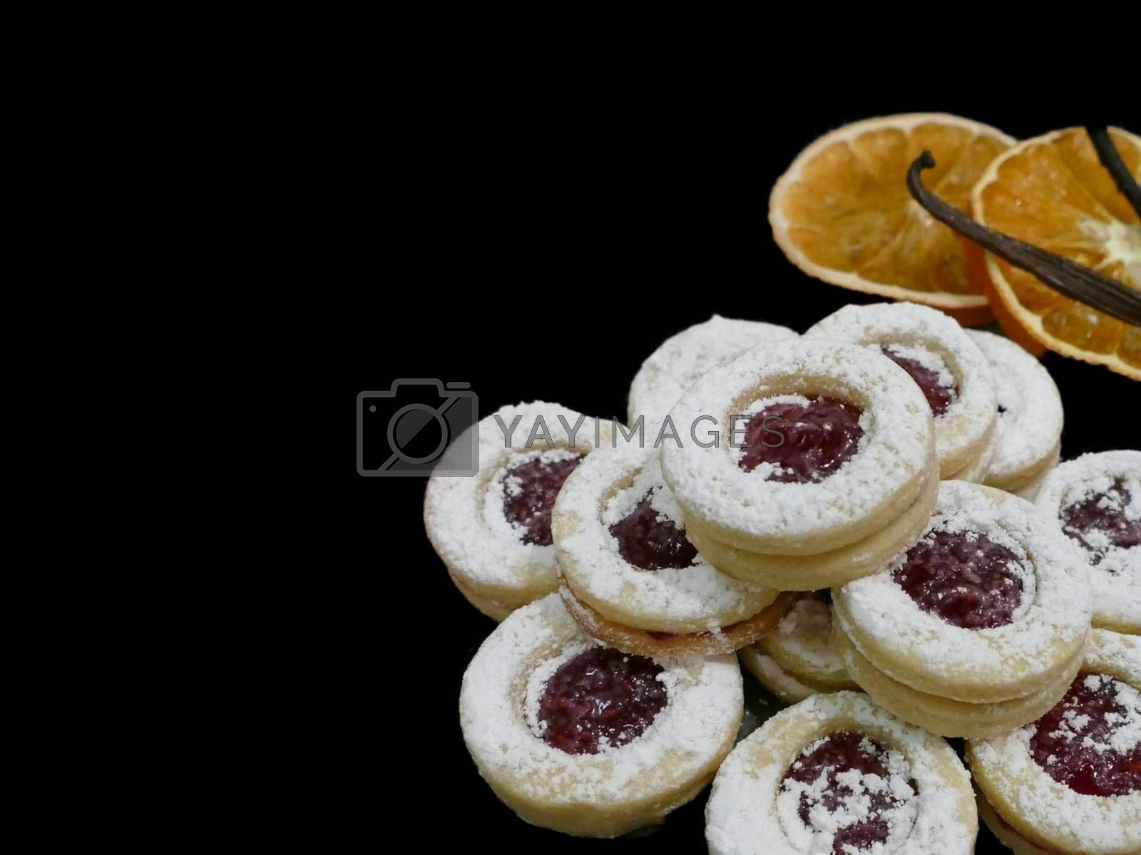 Royalty free image of Strawberry Christmas biscuits and orange slices with cinnamon sticks on a black background by balage941