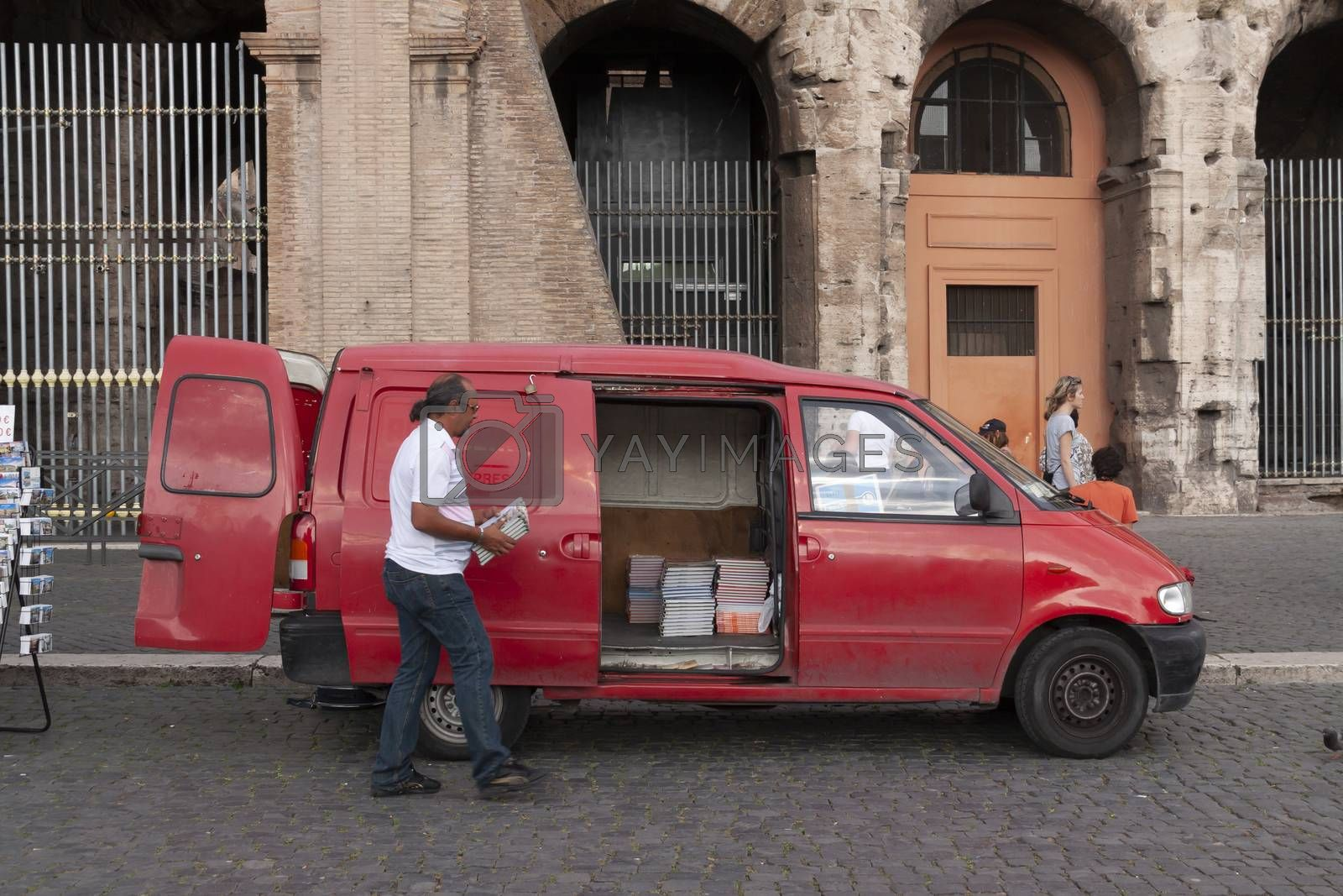 Rome, Italy - June 27, 2010: A man collects maps and guides in a red van, which he has for sale, from a street stall for tourists, next to the Colosseum in Rome.