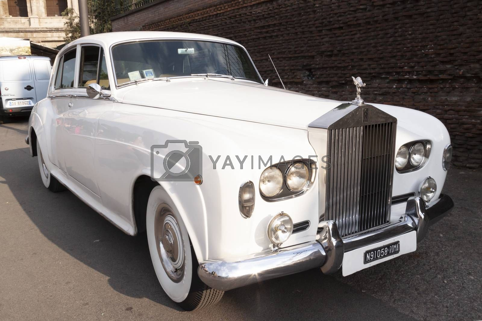 Rome, Italy - June 27, 2010: A luxurious white Rolls-Royce from the 70s, parked on a street in Rome.