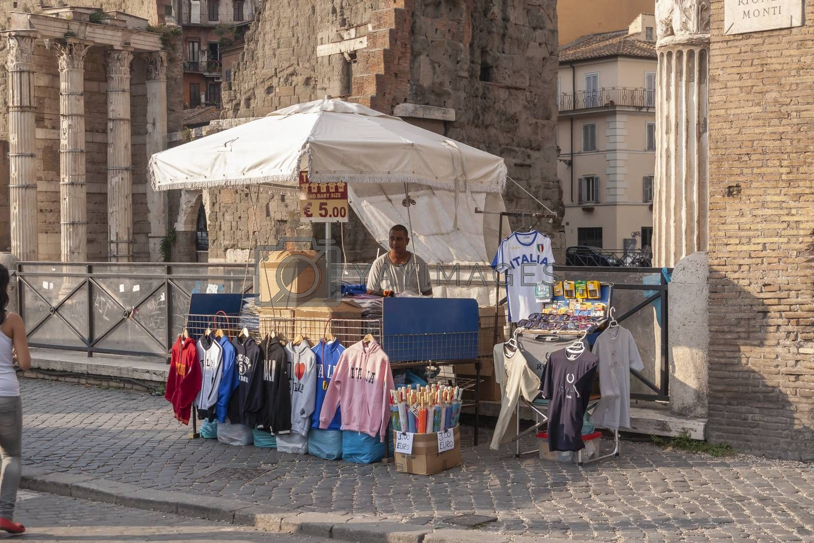 Rome, Italy - June 27, 2010: A man sells T-shirts, sweatshirts and souvenirs to the tourists at his street stall, in the Forum of Augustus area, Rome.