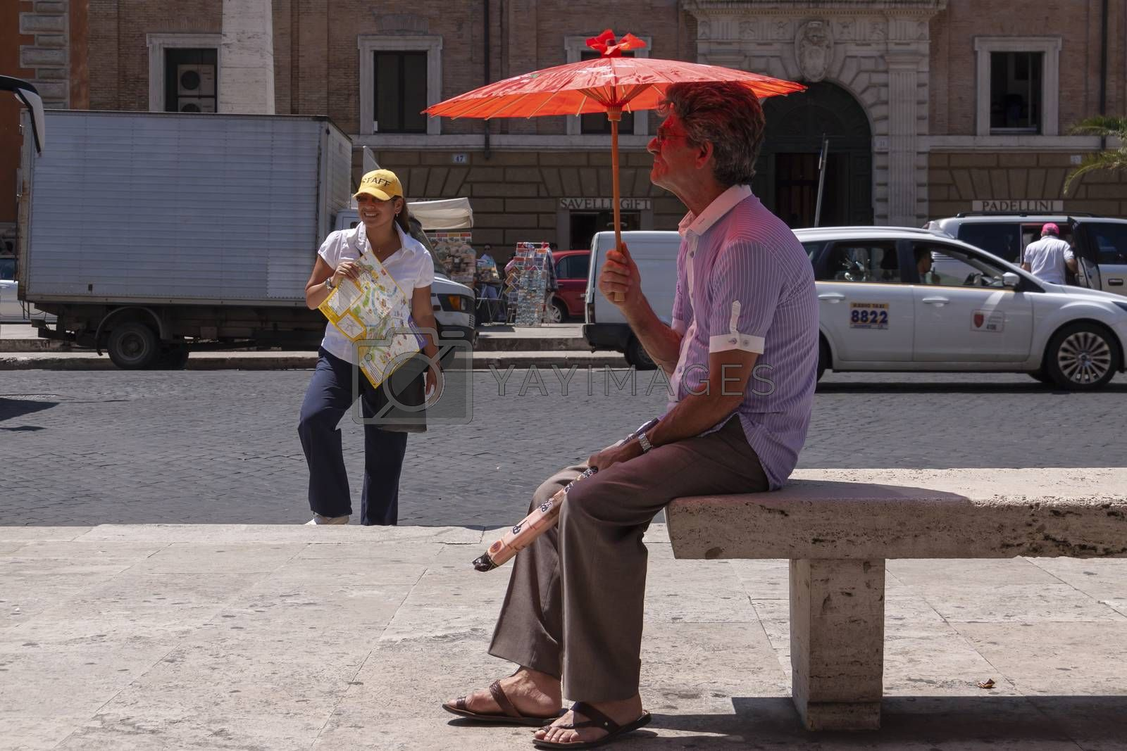 Rome, Italy - June 28, 2010: A street vendor of umbrellas, remains seated on a bench, next to a woman who works as a tour guide in Rome.