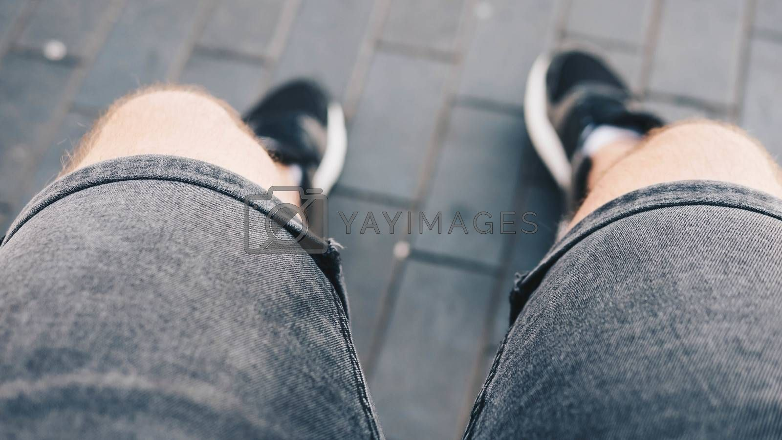 Royalty free image of Male legs in sneakers with blurred background,close-up of the legs of a sitting man. by Andriii_Klapkoo