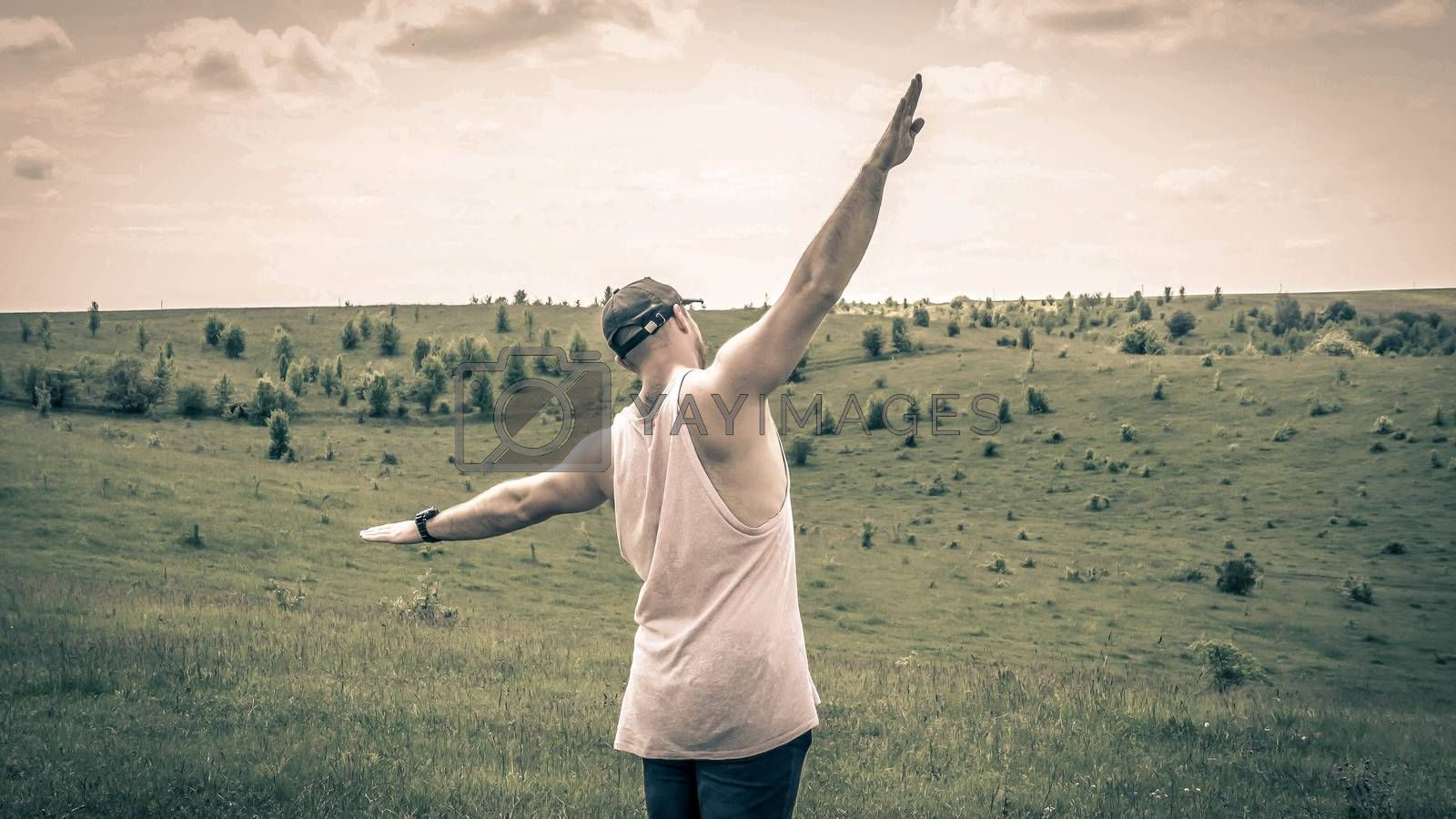 Royalty free image of A dreamy guy in a field with outstretched arms,a free man,a young guy demonstrates freedom,a man pretends to fly by Andriii_Klapkoo