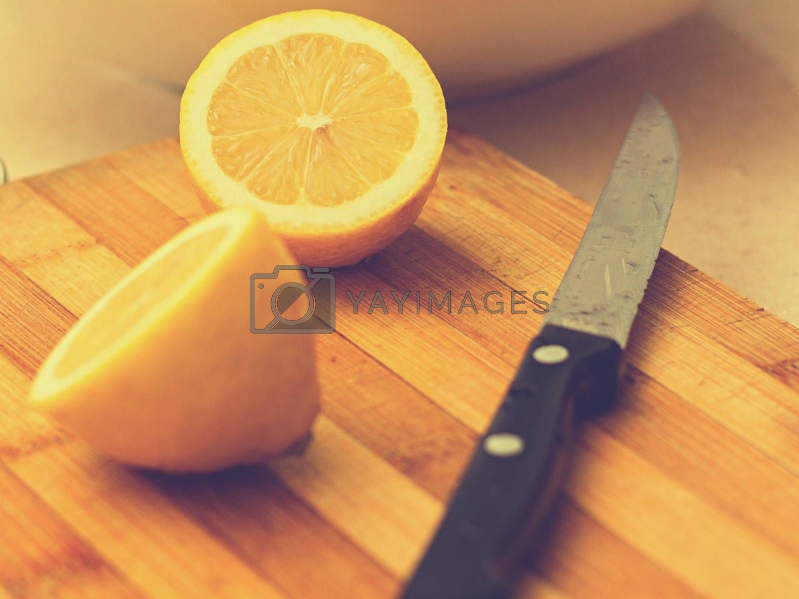 Royalty free image of Two limes sitting on top of a wooden cutting board by balage941