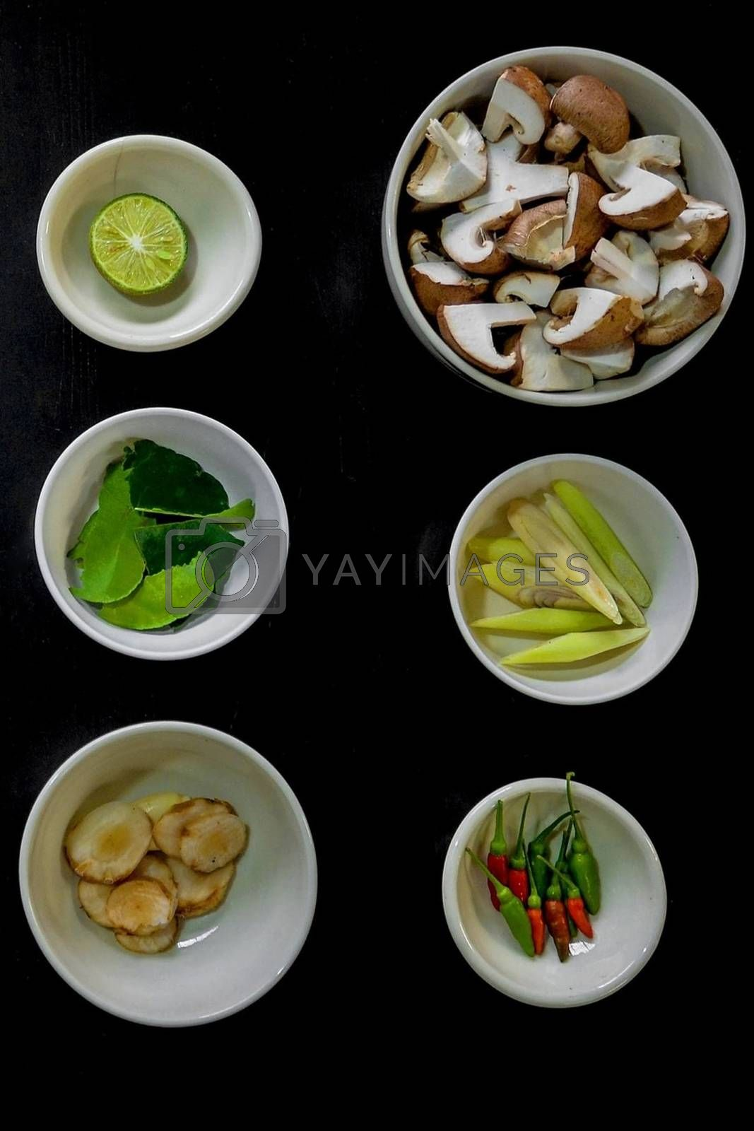 Royalty free image of Chili peppers with lime, mint, mushrooms, cucumber, walnut bowl with black background by balage941