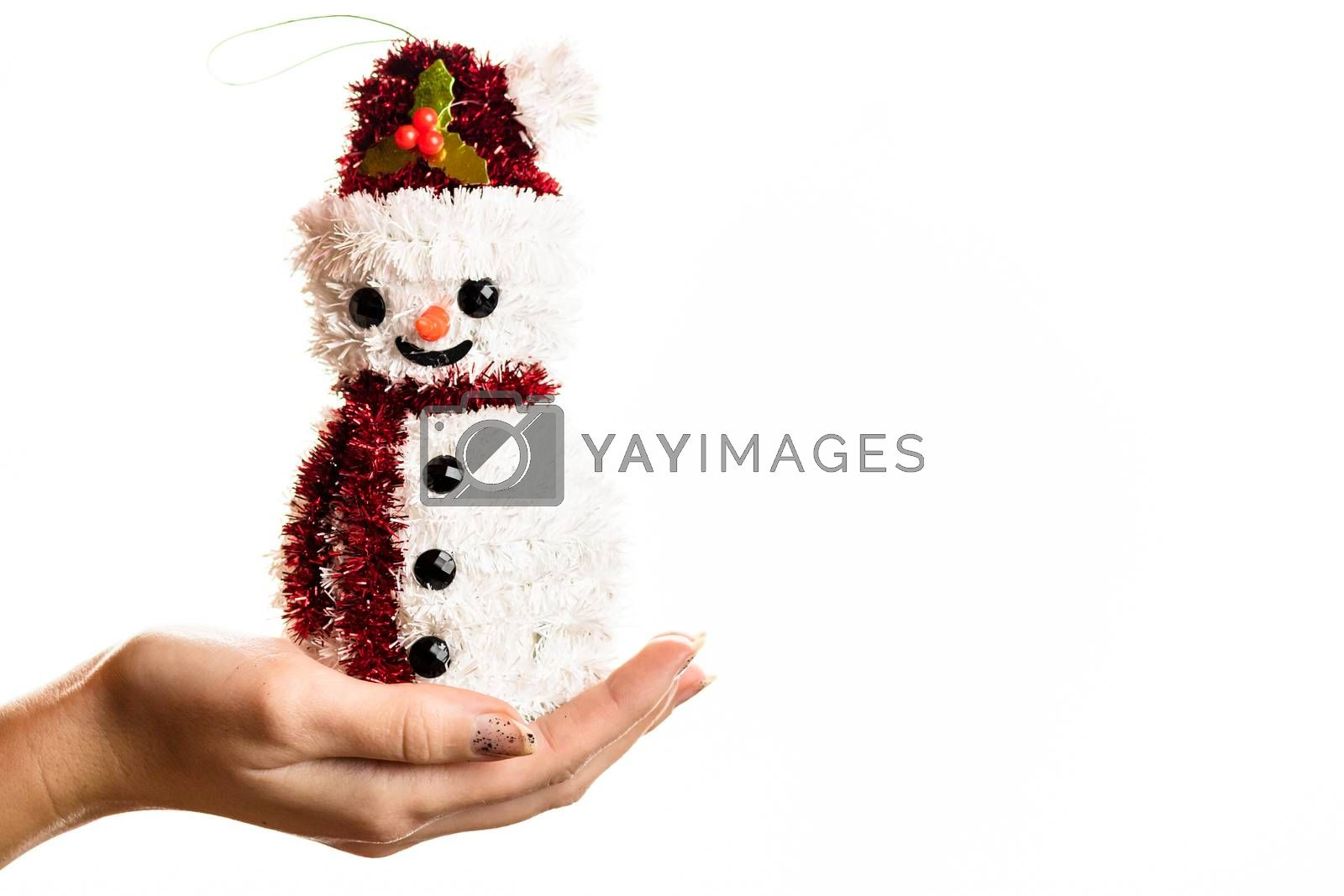 Hand holding Christmas snowman figurine isolated on white background