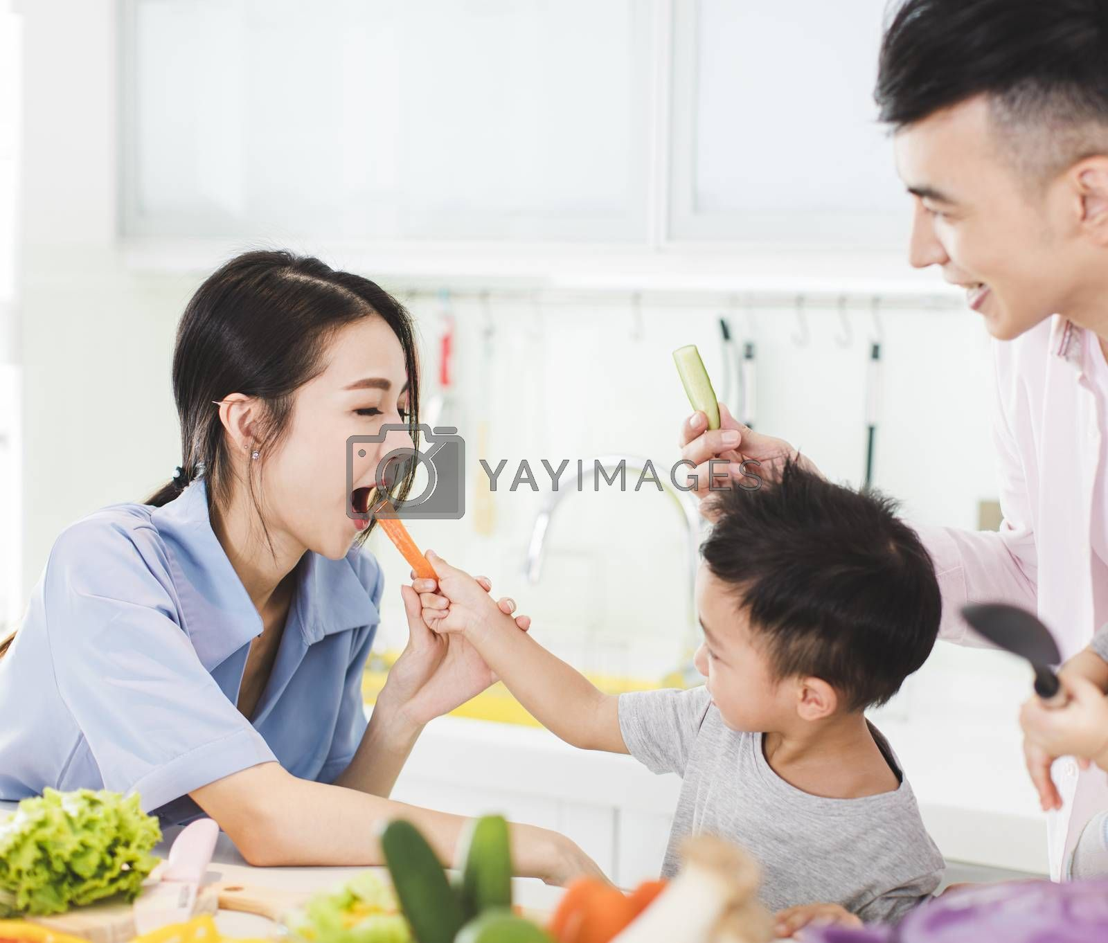 happy little boy feeding mother a piece of  carrot in kitchen