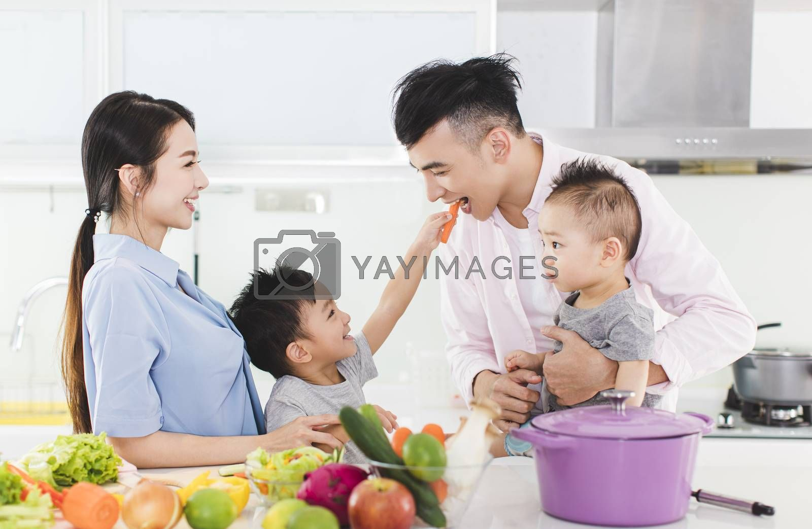 happy little boy feeding father a piece of  carrot in kitchen