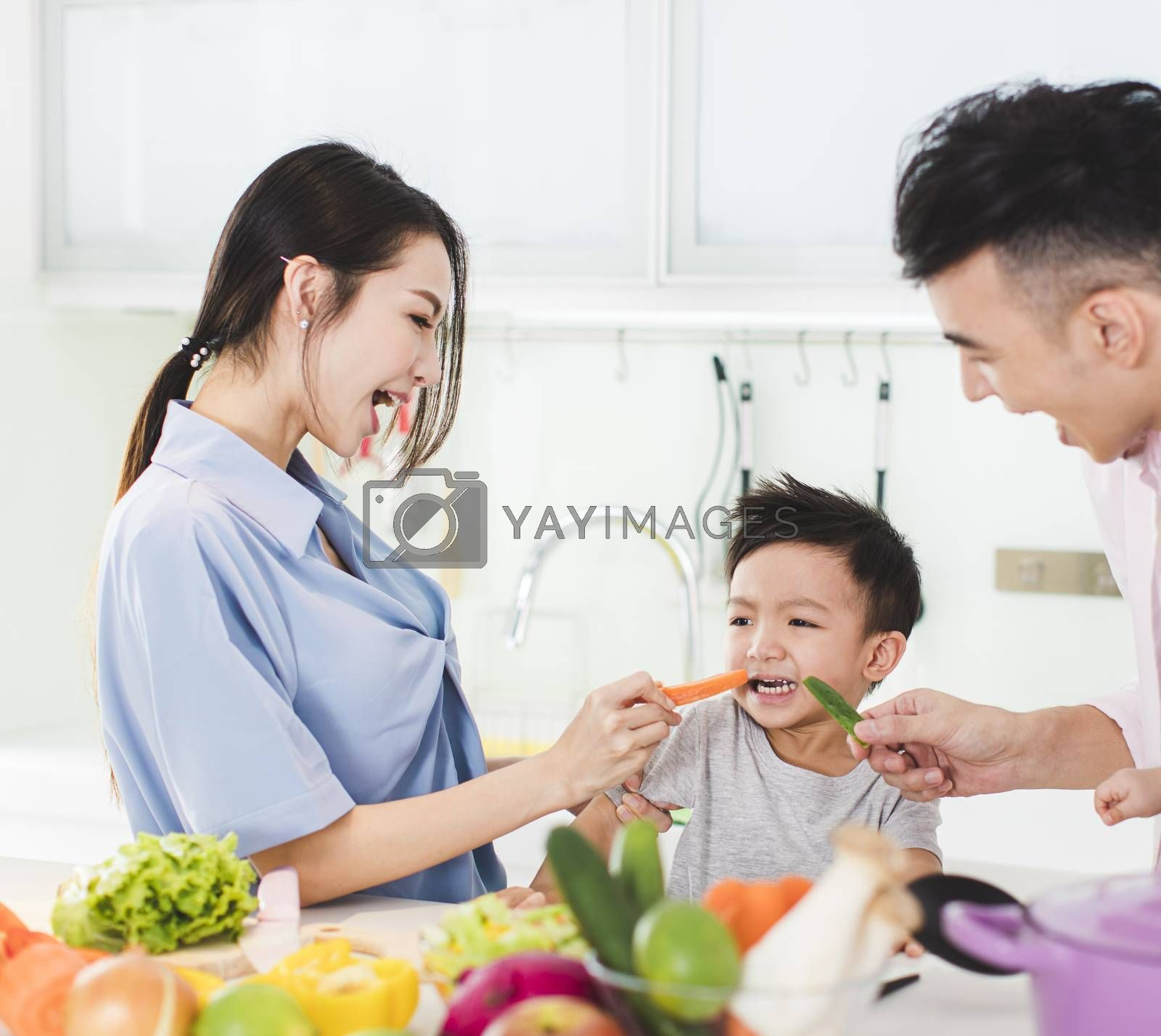 parent feeding boy a piece of  carrot in kitchen by tomwang
