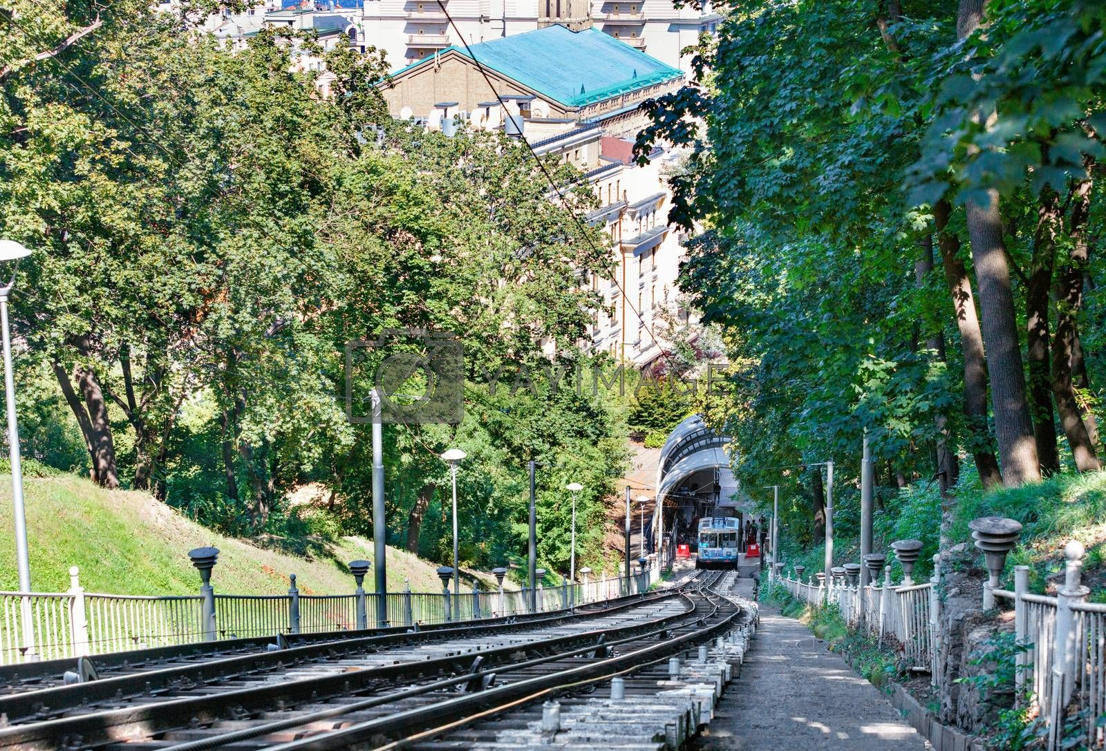 A cable funicular, surrounded by the green foliage of a summer park, picks up passengers at the bottom station to lift them up the mountainside.