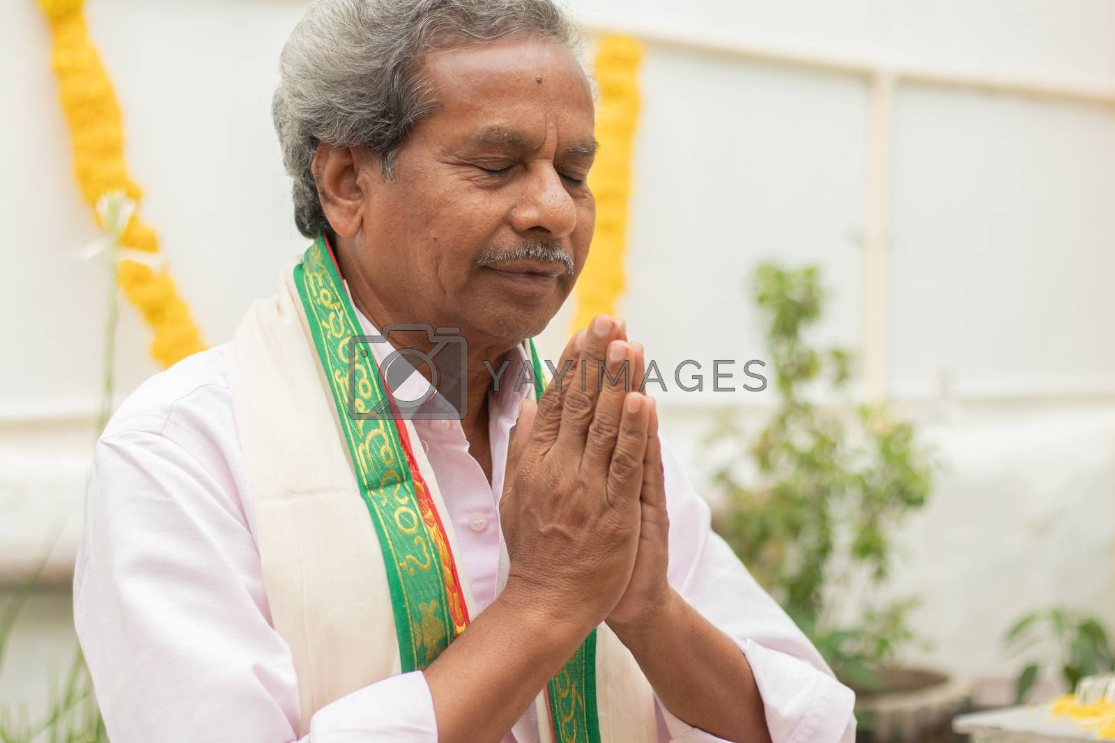 Elder man in closed eyes offering Prayer by namaste gesture praying to god at home in traditional dress during rituals