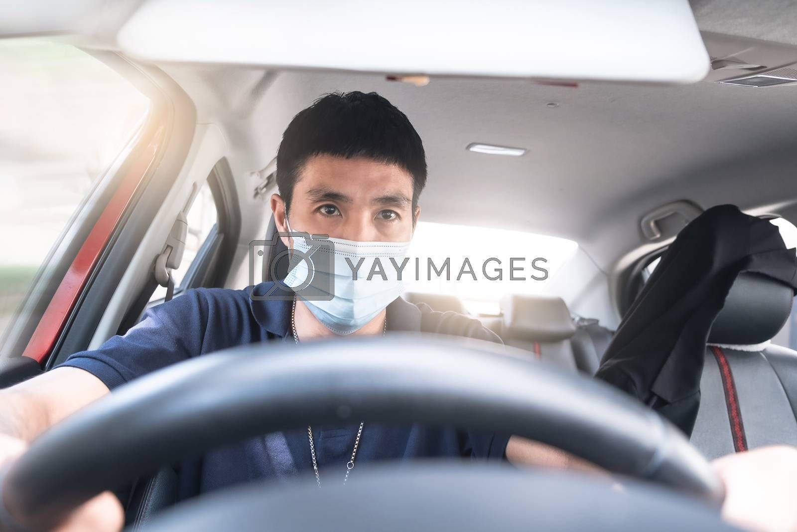 Young Asian man wearing surgical mask driving car so panic shock by oatzpenzstudio