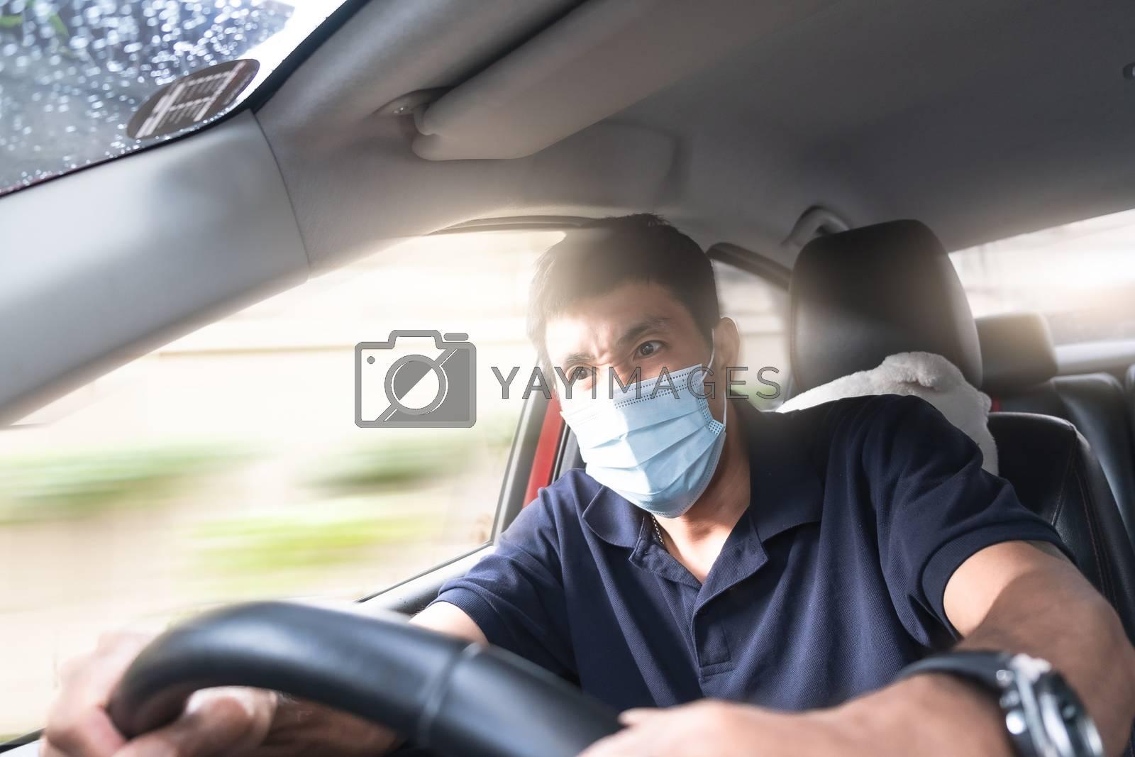 Young Asian man wearing surgical mask driving car so panic shock by oatzpenzstudio