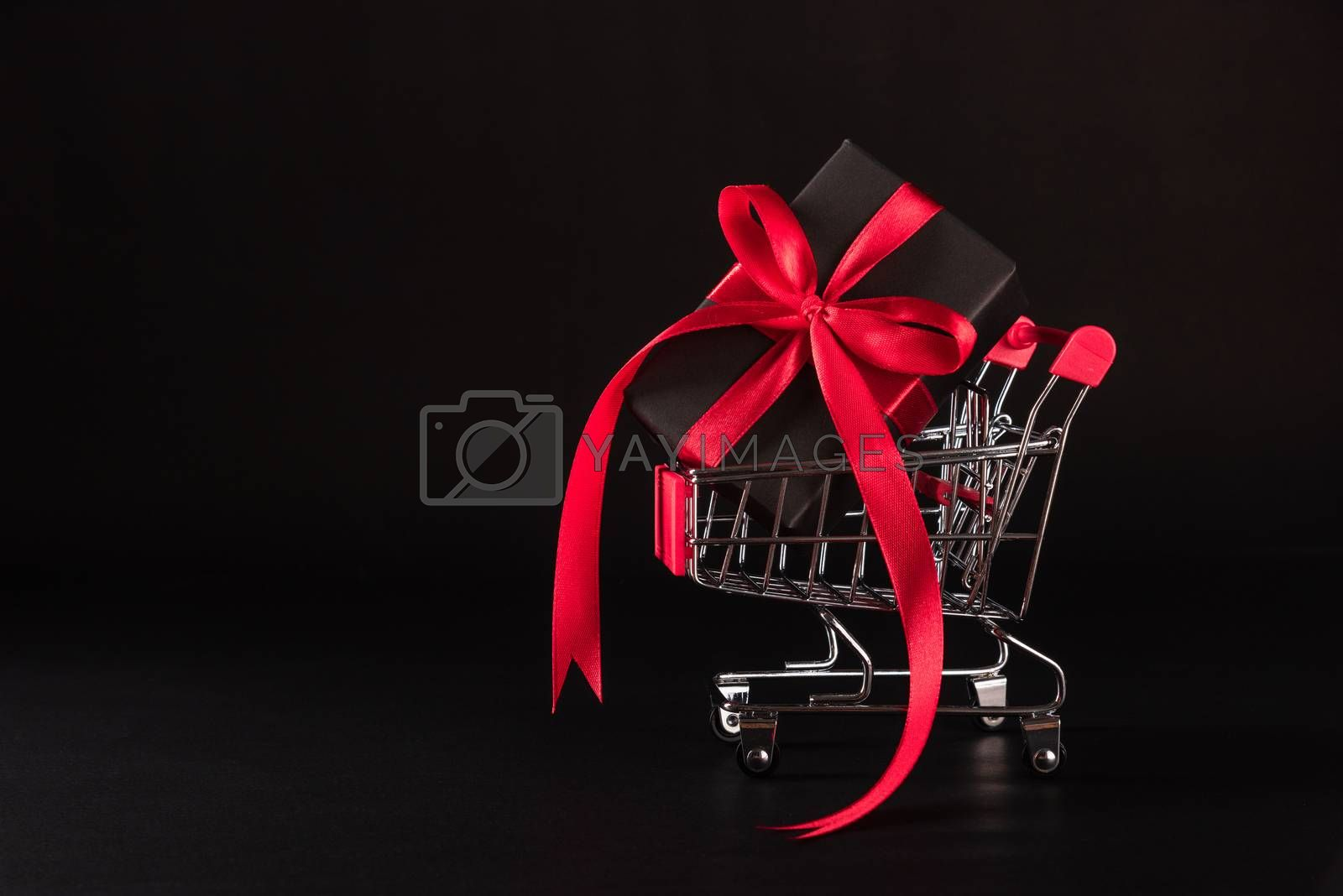Black Friday sale shopping concept, Gift box wrapped black paper and red bow ribbon present in the shopping cart, studio shot on black background