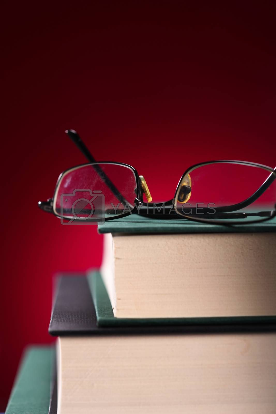glasses on top of a pile of old books