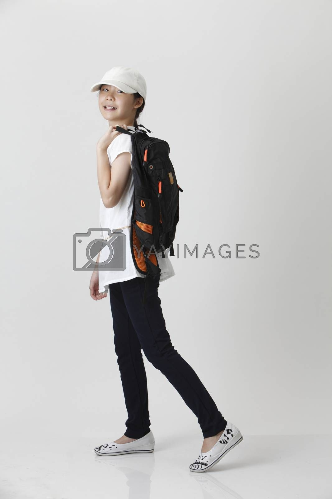 girl with backpack and cap in the walking position