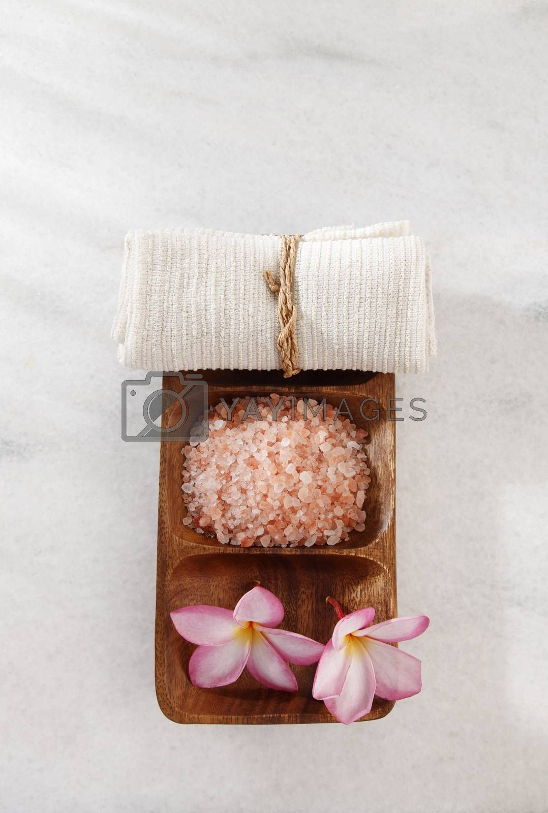 frangipani flower,salt and towel in a wooden bowl