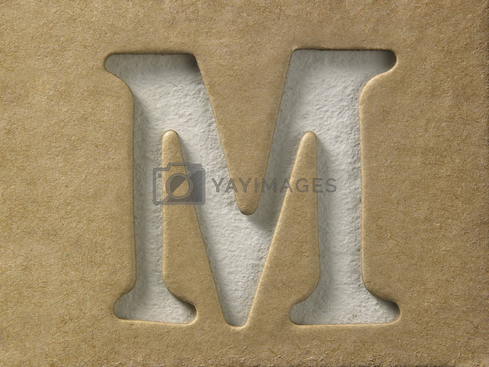cut out alphabet m on the brown cardboard