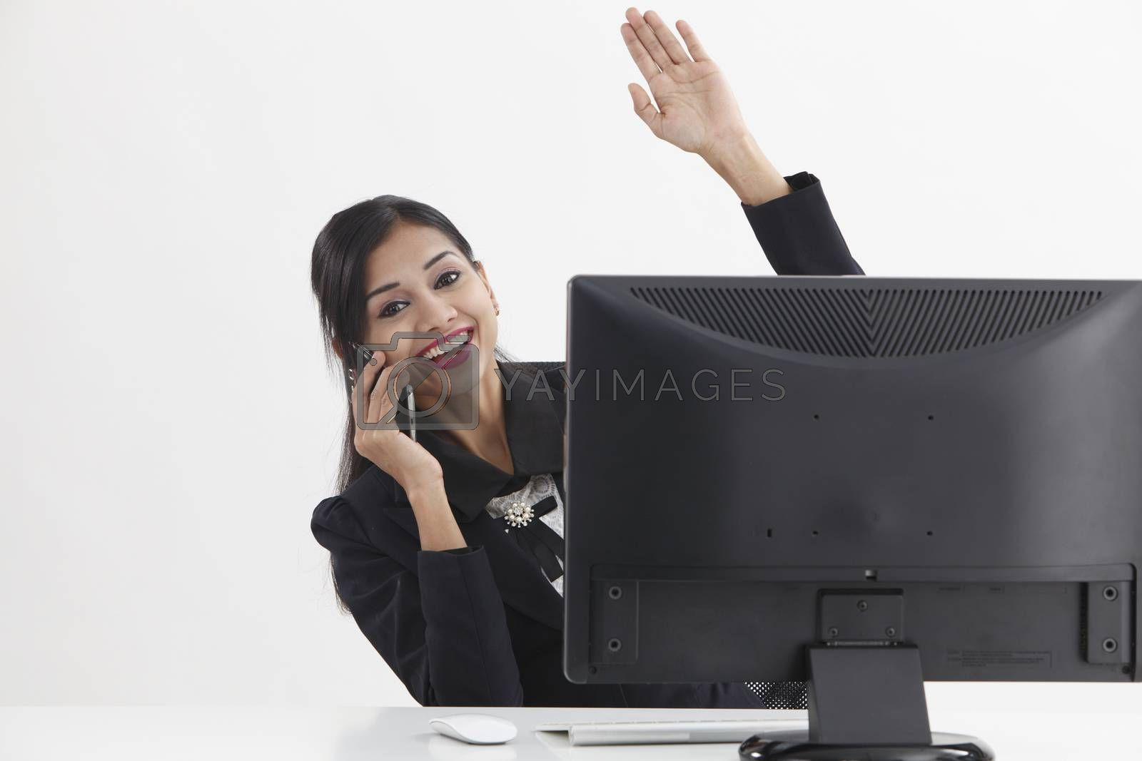 business woman sitting in front of computer,talking and waving to camera