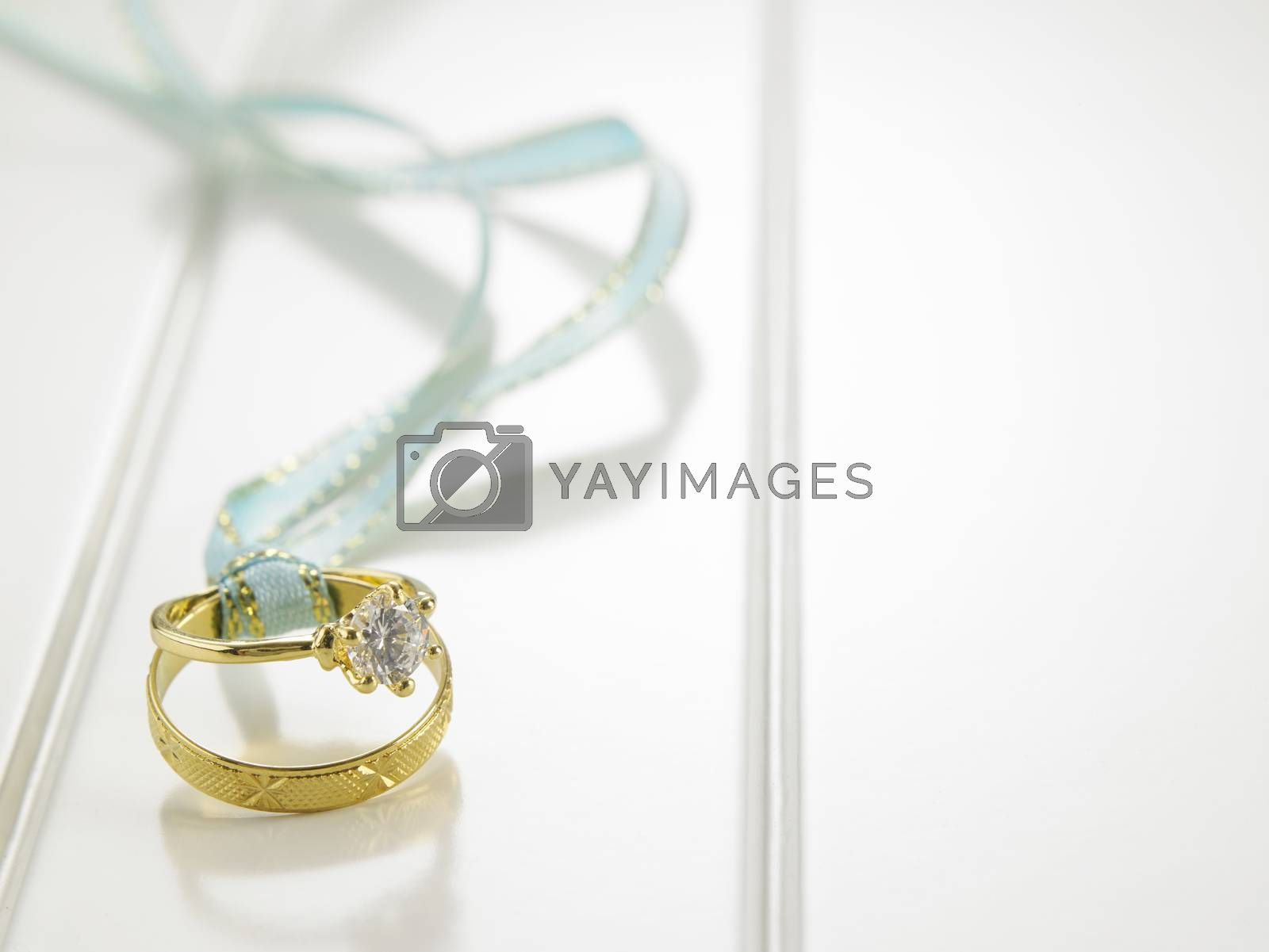 Wedding rings connected with green ribbon