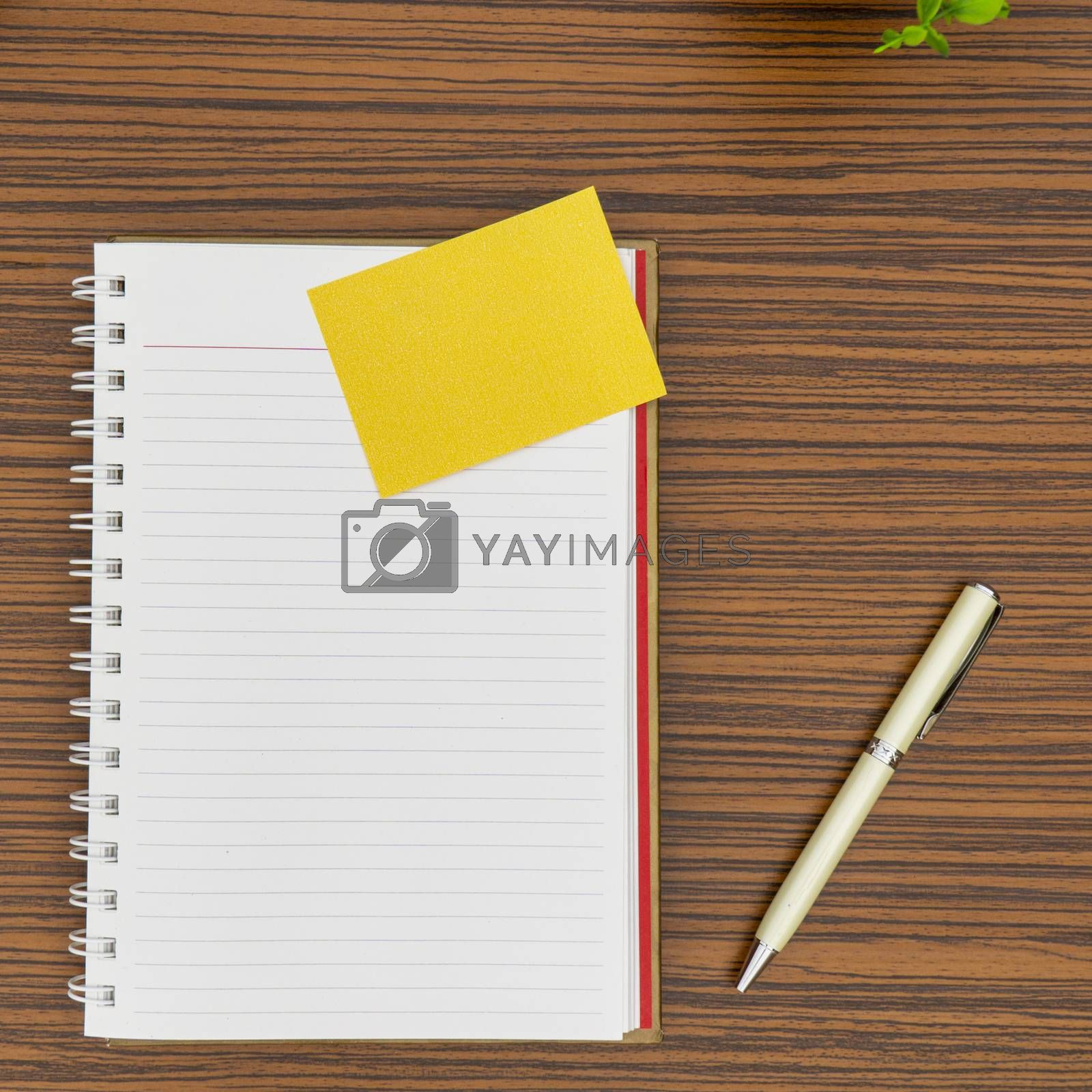 Personal notepad, yellow paper note and a pen on a zebra wood brown striped table.