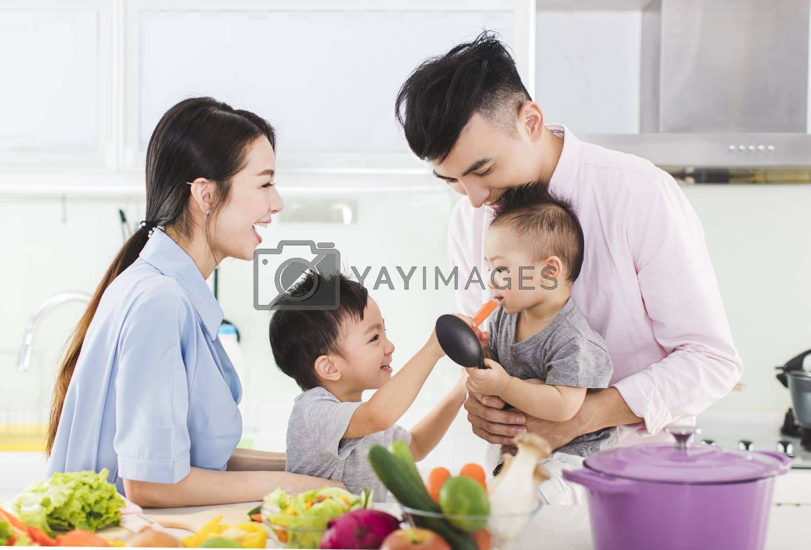 parent and boy feeding son a piece of  carrot in kitchen